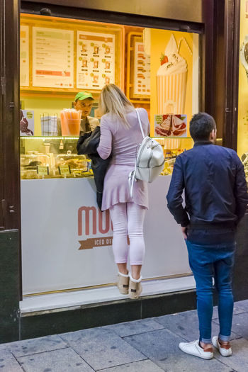 A young woman buying an ice cream in Madrid. City City Street Man Travel Travelling Woman Architecture Building Exterior Buying Casual Clothing Customer  Food For Sale Full Length Leisure Activity Lifestyles Outdoors People Real People Rear View Retail  Small Business Standing Street Travel Destinations