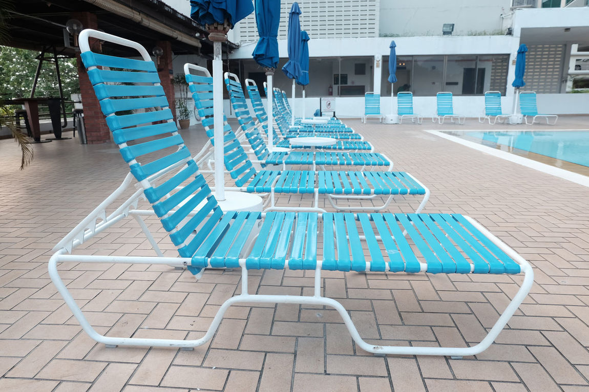 blue rubber bench near the pool Absence Architecture Bench Blue Building Exterior Built Structure Chair City Life Day Diminishing Perspective Empty Footpath No People Outdoors Paving Stone Seat Sidewalk Sidewalk Cafe Tourism