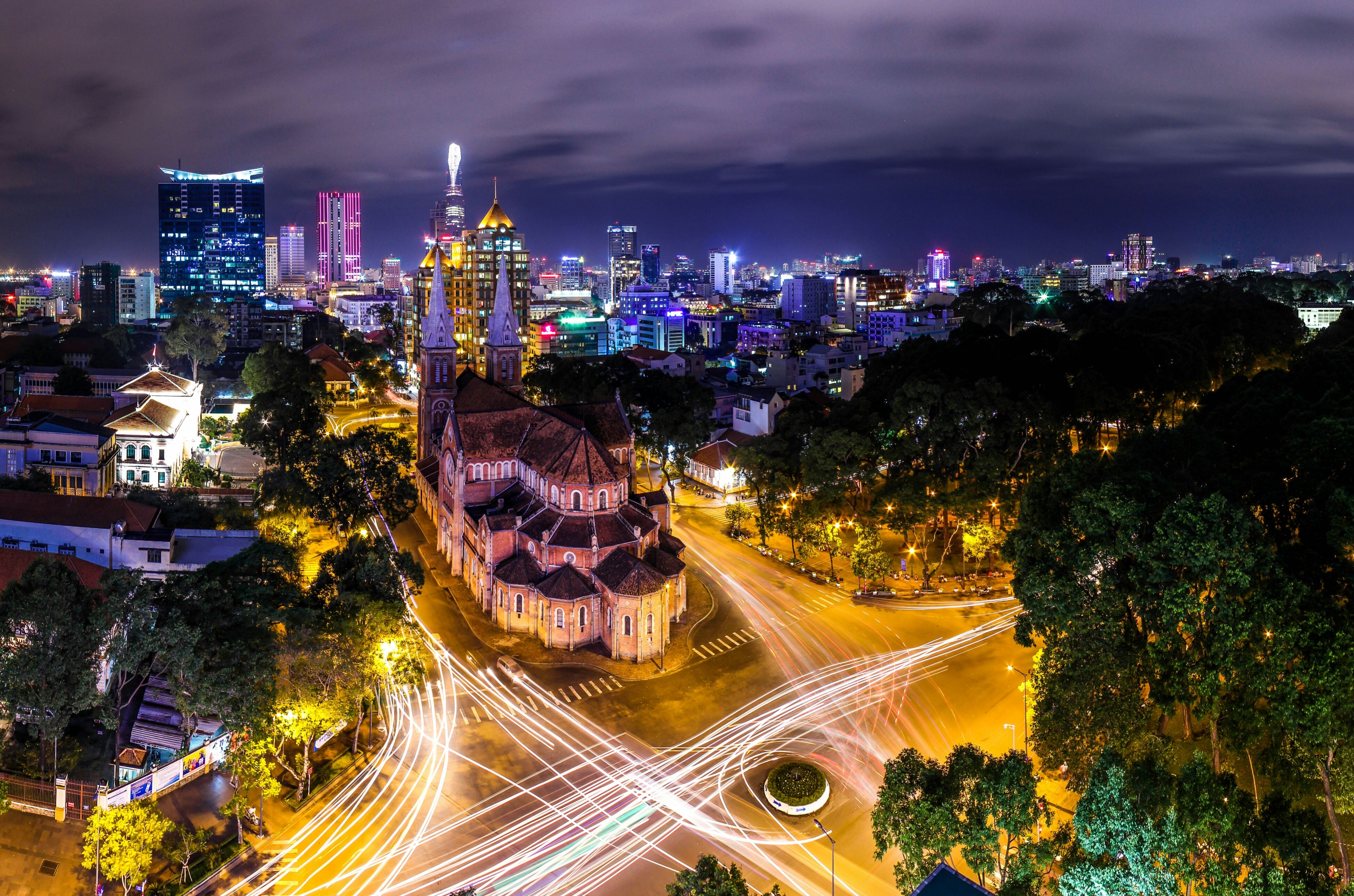 illuminated, city, building exterior, night, architecture, built structure, cityscape, high angle view, light trail, transportation, city life, road, long exposure, sky, skyscraper, street, modern, tree, car, traffic