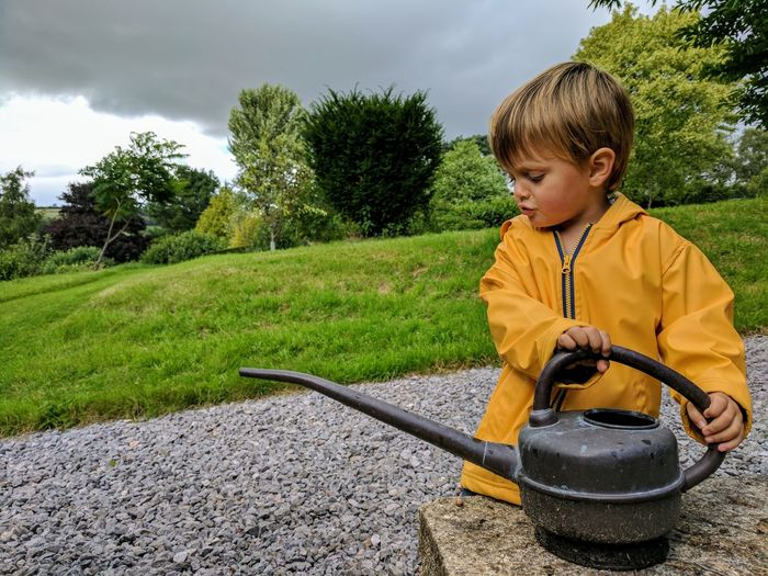 Watering can. Childhood Child Boys Children Only Males  One Person One Boy Only Tree Outdoors People Day Grass Water Sand Pail And Shovel Sky Pouring Wateringcan Watering Cans Play