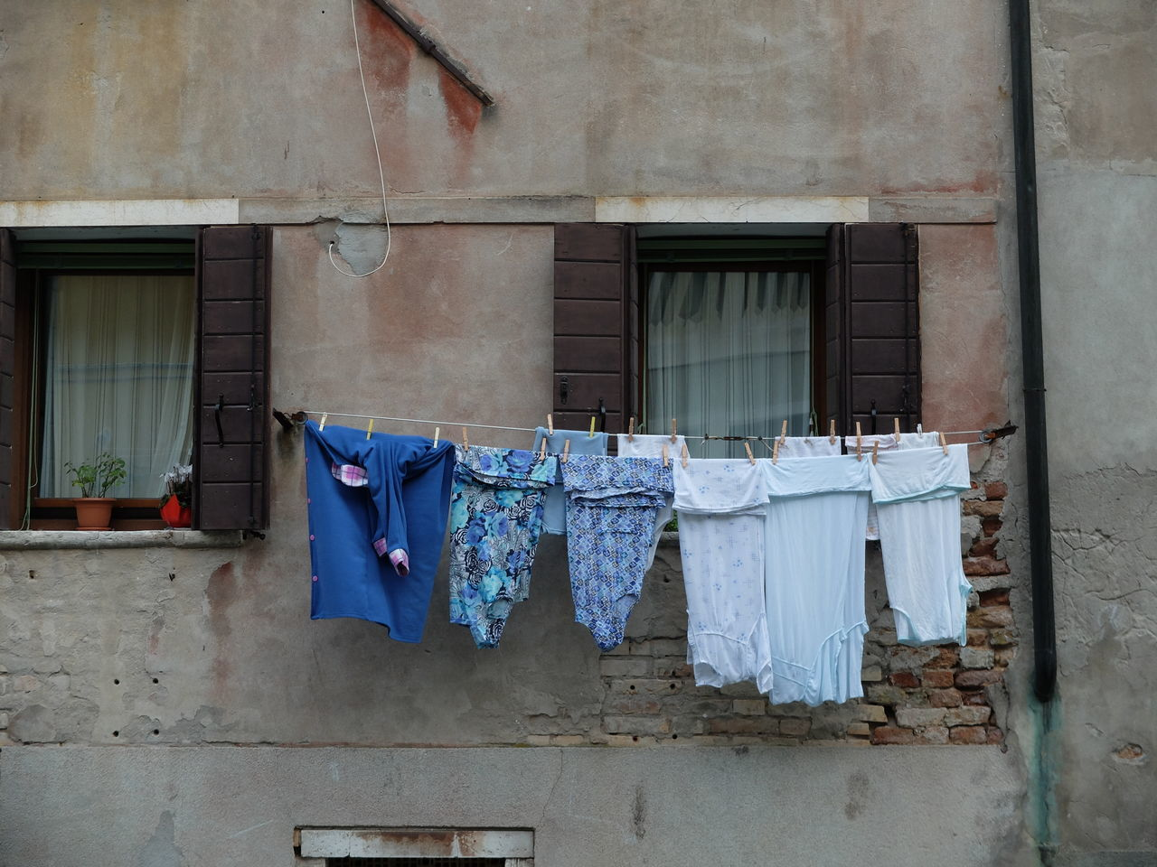 architecture, clothesline, built structure, building exterior, drying, laundry, building, window, house, no people, hanging, residential building, abandoned, outdoors, day, cloth