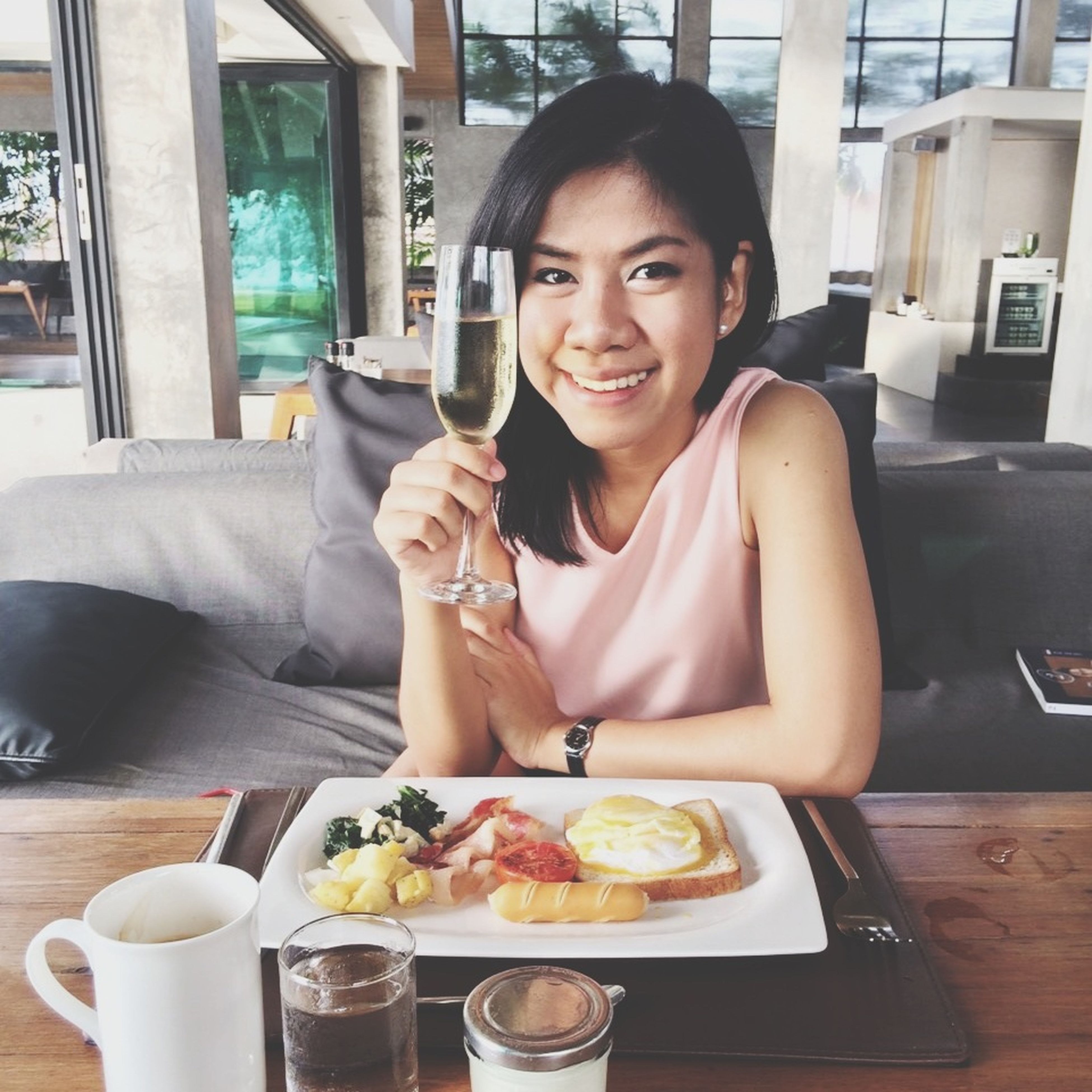 food and drink, indoors, sitting, lifestyles, food, person, young adult, drink, table, freshness, leisure activity, casual clothing, young women, restaurant, waist up, holding, front view, portrait