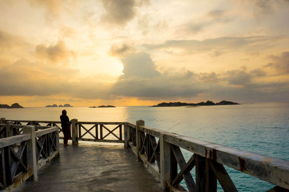 A women facing beautiful sunrise moment Beauty In Nature Calm Cloud Cloud - Sky Cloudy Horizon Over Water Idyllic Jetty Nature Non-urban Scene Ocean Orange Color Outdoors Pier Remote Rippled Scenics Sea Sky Sunset The Way Forward Tranquil Scene Tranquility Water