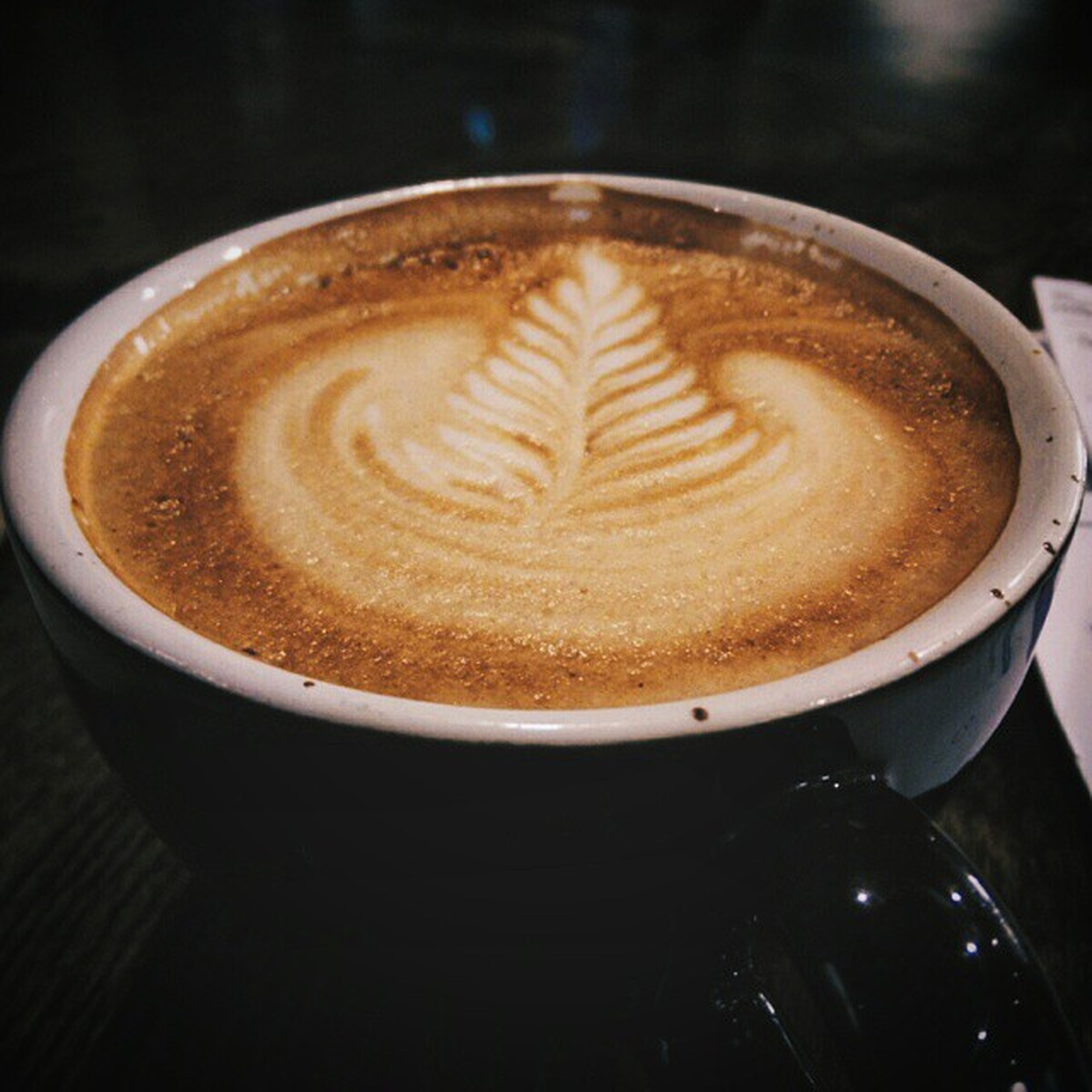 coffee cup, drink, refreshment, coffee - drink, froth art, frothy drink, cappuccino, food and drink, saucer, coffee, table, indoors, close-up, still life, freshness, latte, high angle view, cup, spoon, heart shape