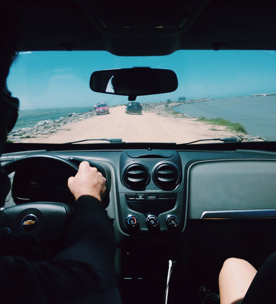 vehicle interior, car interior, car, transportation, steering wheel, one person, driving, real people, men, mode of transport, human hand, dashboard, land vehicle, day, human body part, windscreen, speedometer, close-up, outdoors, sky, people