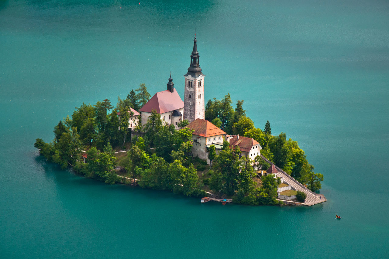 The Church of the Assumption in the middle of Lake Bled in Slovenia. The only way of getting to this church is via kayak or one of the traditional pletna's (that can be seen in the bottom right of the photo). Architecture Bled Blue Building Exterior Built Structure Church Church Of The Assumption Nature Outdoors Place Of Worship Religion Slovenia Spirituality The Great Outdoors - 2016 EyeEm Awards Town Travel Destinations Water