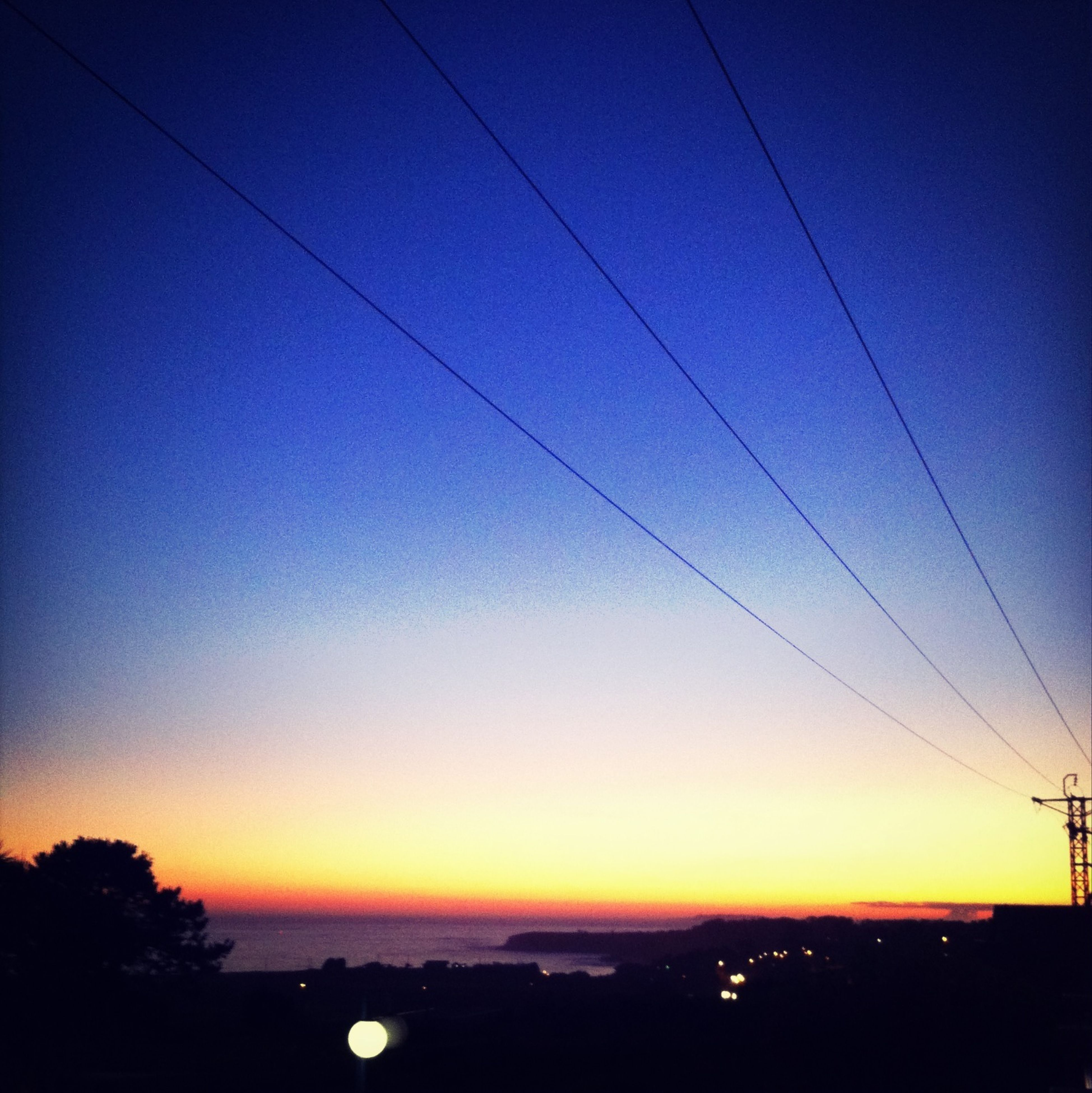 sunset, silhouette, power line, tranquility, tranquil scene, scenics, electricity, electricity pylon, beauty in nature, power supply, orange color, sky, cable, nature, clear sky, idyllic, sun, connection, blue, dusk