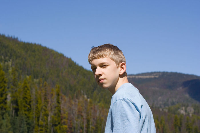 teenager in front of a forest Adolescence  Attitude Blond Hair Bored Boy Boys Casual Clothing Caucasian Clear Sky Cool Cool Attitude Facial Experiments Facial Expression Forest Head And Shoulders Low Angle View One Teenage Boy Only Outdoors Puberty Real People Serious Standing Teenage Boys Teenager Woods