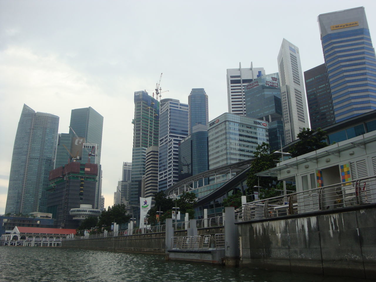 architecture, built structure, building exterior, skyscraper, city, river, modern, water, sky, outdoors, day, no people, waterfront, travel destinations, low angle view, growth, tall, urban skyline, tree, cityscape