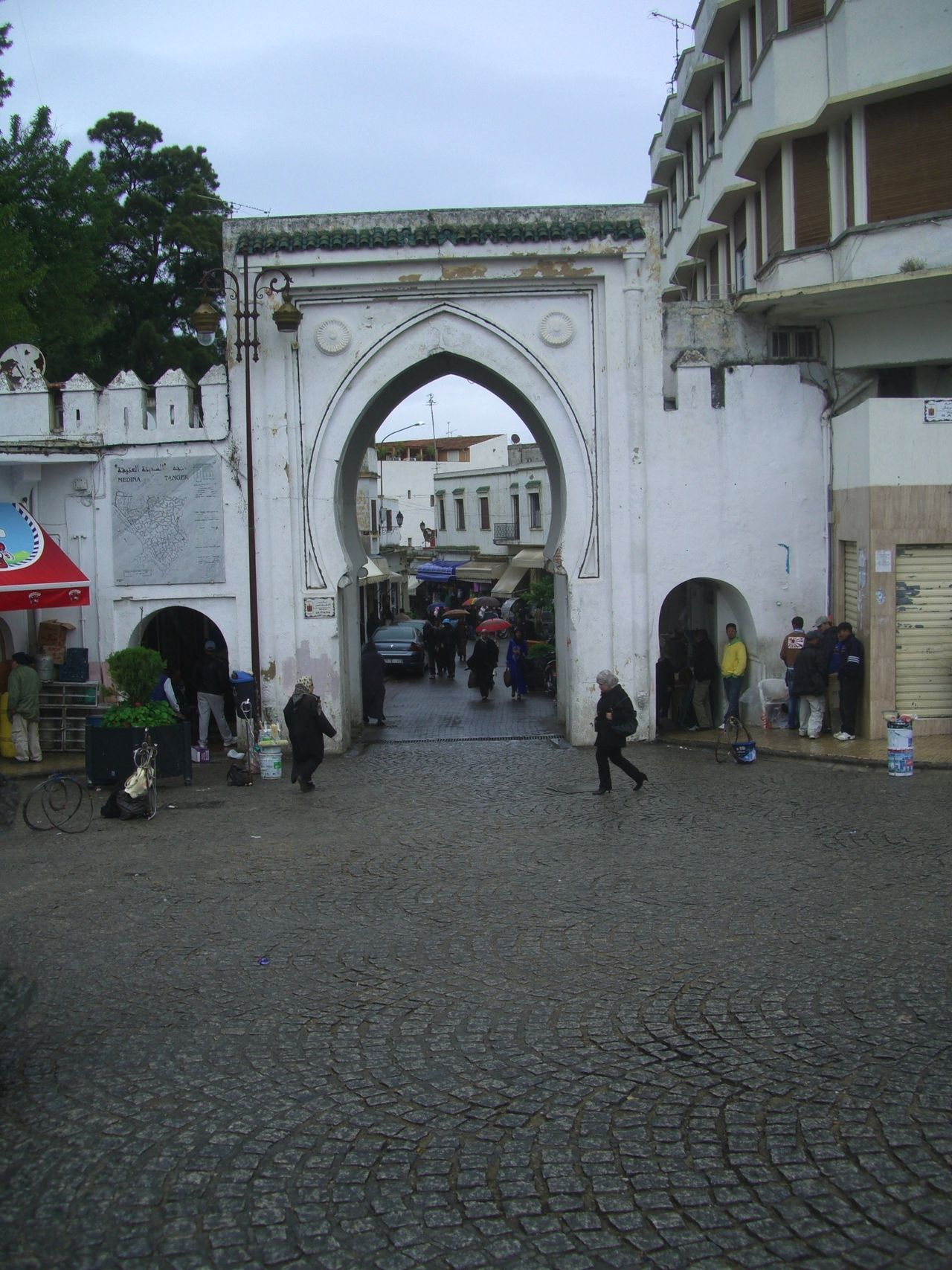 Entrance to Medina from Grand Socco Arch Architecture Building Exterior Built Structure Cloudy Sky Composition Entrance Famous Place Full Frame Gateway Gateway Arch Incidental People Medina Moroccan Architecture Moroccan Style Morocco Old City Outdoor Photography Tangier Tourist Attraction  Tourist Destination Tree White Walls