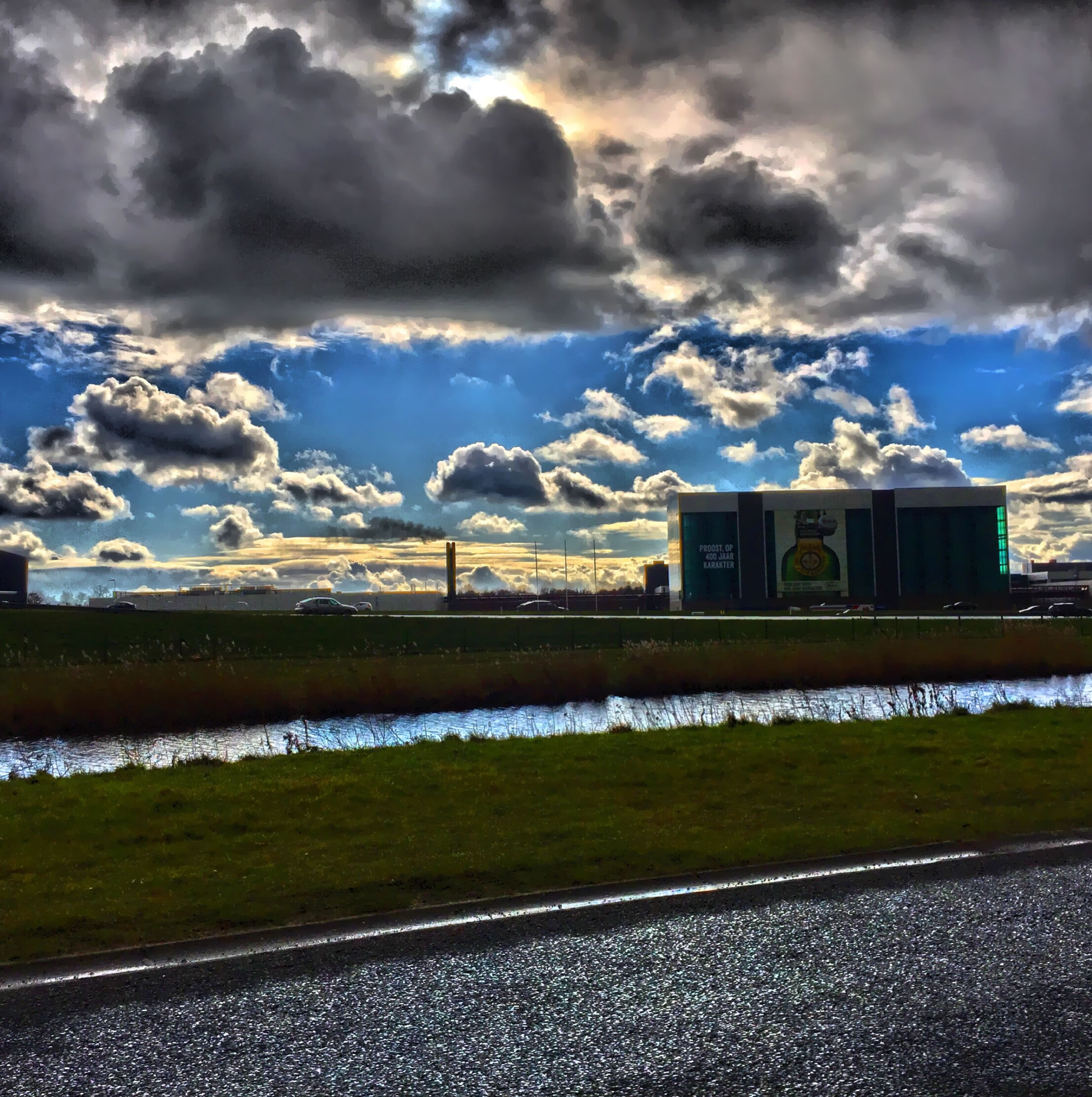 sky, cloud - sky, cloudy, water, building exterior, cloud, built structure, architecture, weather, road, nature, tranquility, beauty in nature, tranquil scene, river, lake, scenics, landscape, grass, field