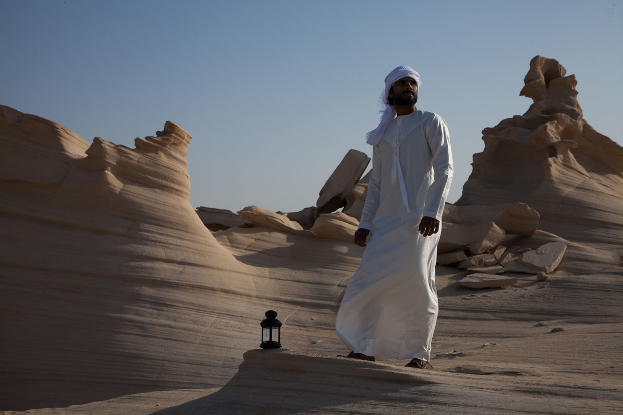 Arid Climate Beauty In Nature Day Desert Full Length Leisure Activity Lifestyles Men Nature One Person Outdoors People Physical Geography Real People Rock - Object Sand Sculpture Sky Standing Statue Travel Destinations Women Young Adult