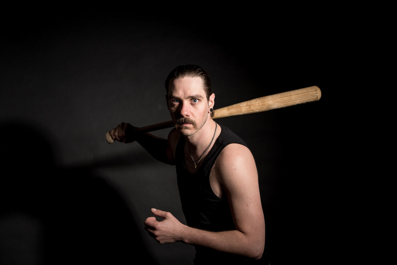 Clichéd studio shot of an angry man with a baseball bat looking for a fight Adult Aggression  Aggressive Aggressive Guy Anger Baseball Bat Fight Gang Looking At Camera Man Mustache One Person Strength Studio Shot Trouble Weapon Young Adult