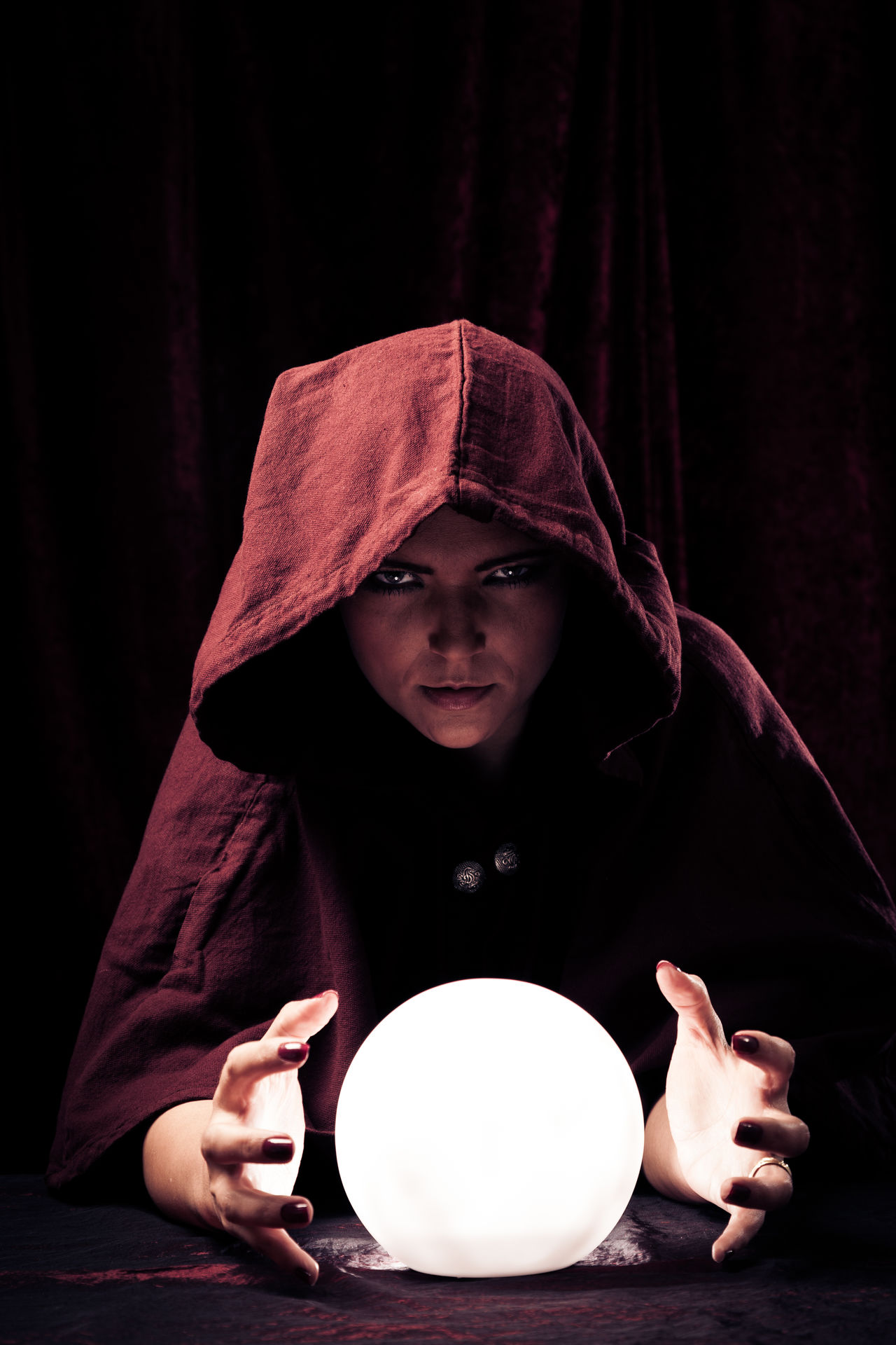 Studio shot of fortune teller. Crystal Crystal Ball Forecast Fortune Teller Fortune Telling Future Hood Magic Paranormal Portrait Psychic Medium Red Spooky Studio Shot Vision Woman Women Young Women