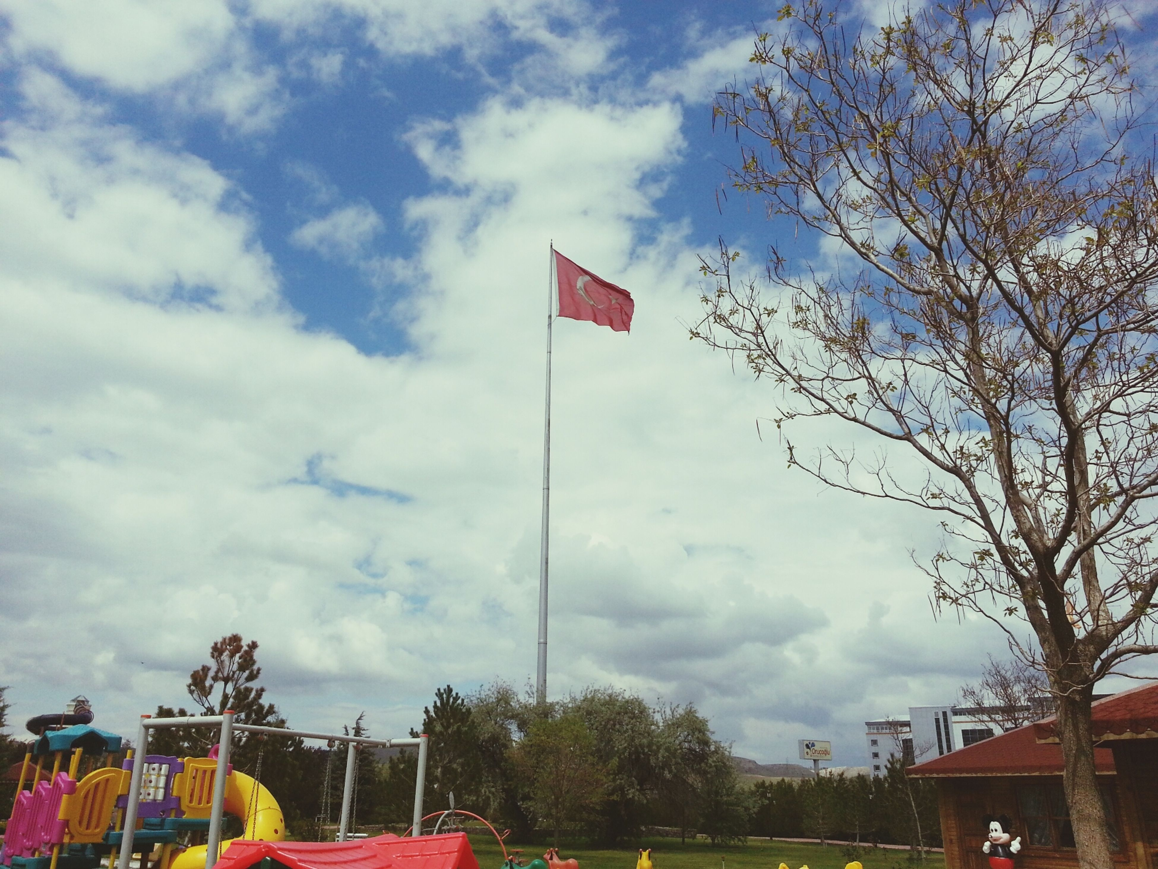 flag, sky, patriotism, national flag, identity, building exterior, cloud - sky, low angle view, architecture, built structure, american flag, tree, cloud, cloudy, red, day, city, road sign, bare tree, outdoors