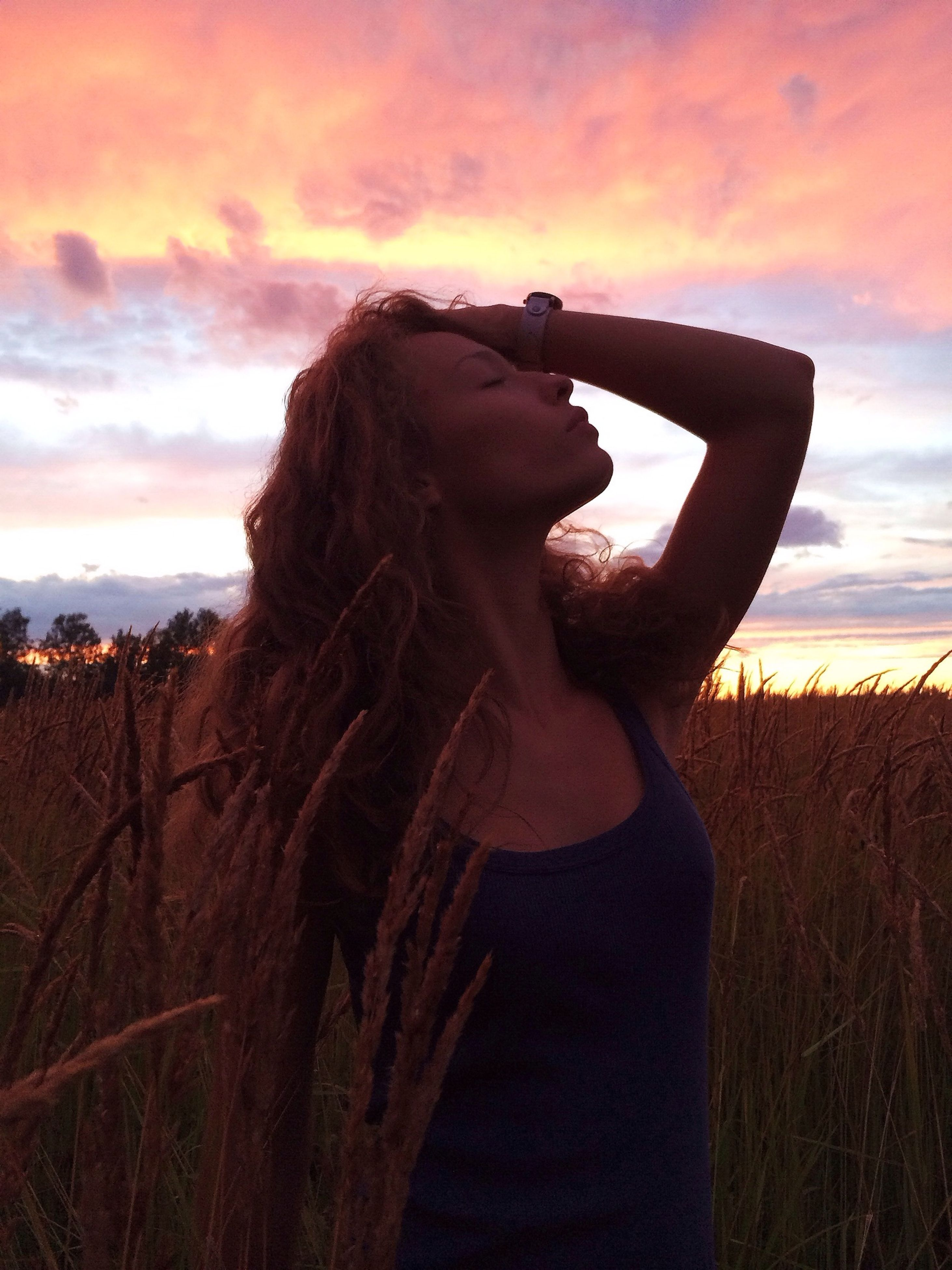 sunset, sky, lifestyles, leisure activity, field, cloud - sky, standing, waist up, orange color, cloud, long hair, nature, three quarter length, tranquility, young women, beauty in nature, outdoors, landscape