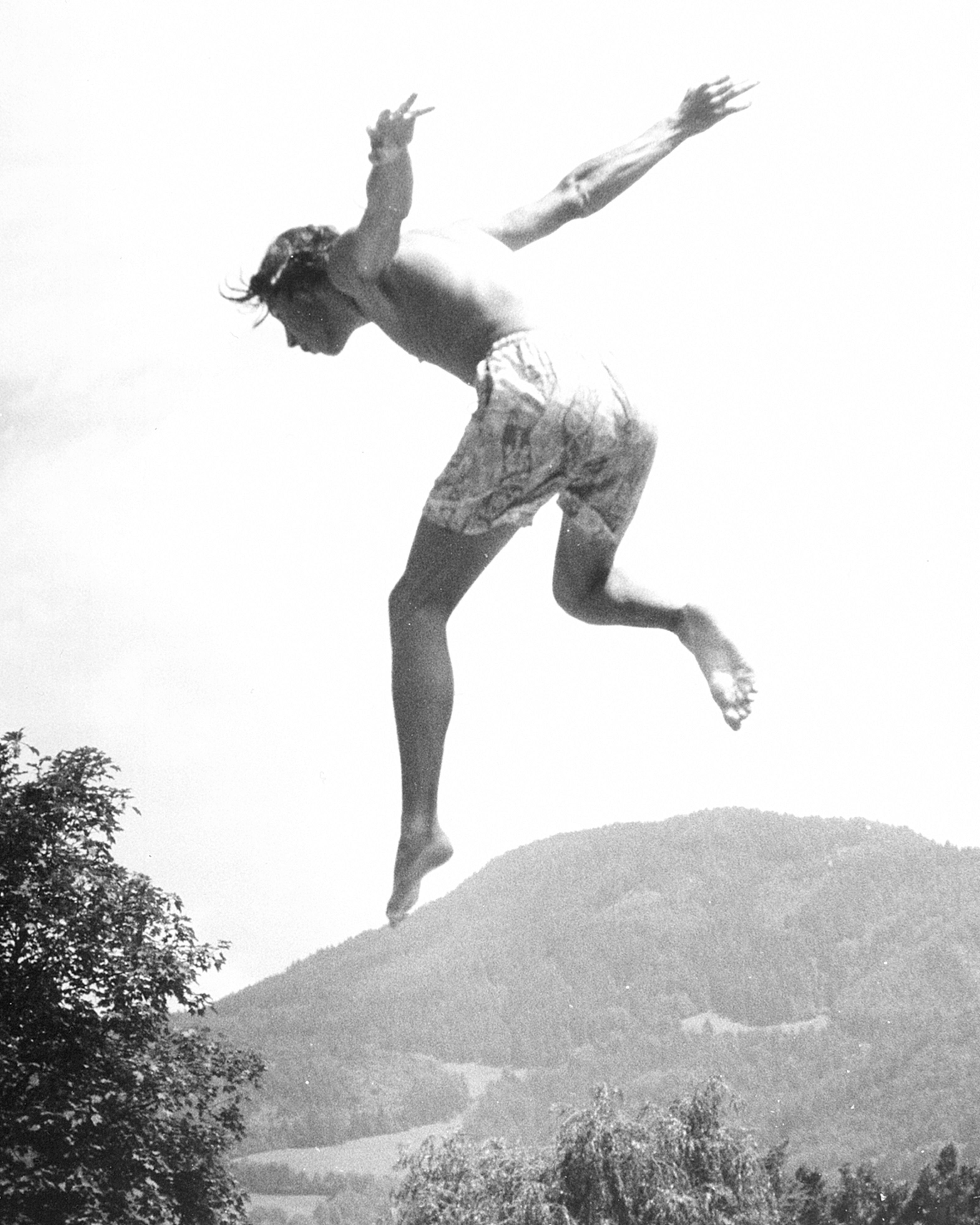 full length, jumping, mid-air, lifestyles, leisure activity, low angle view, clear sky, freedom, arms outstretched, carefree, tree, vitality, arms raised, nature, men, side view, enjoyment, day