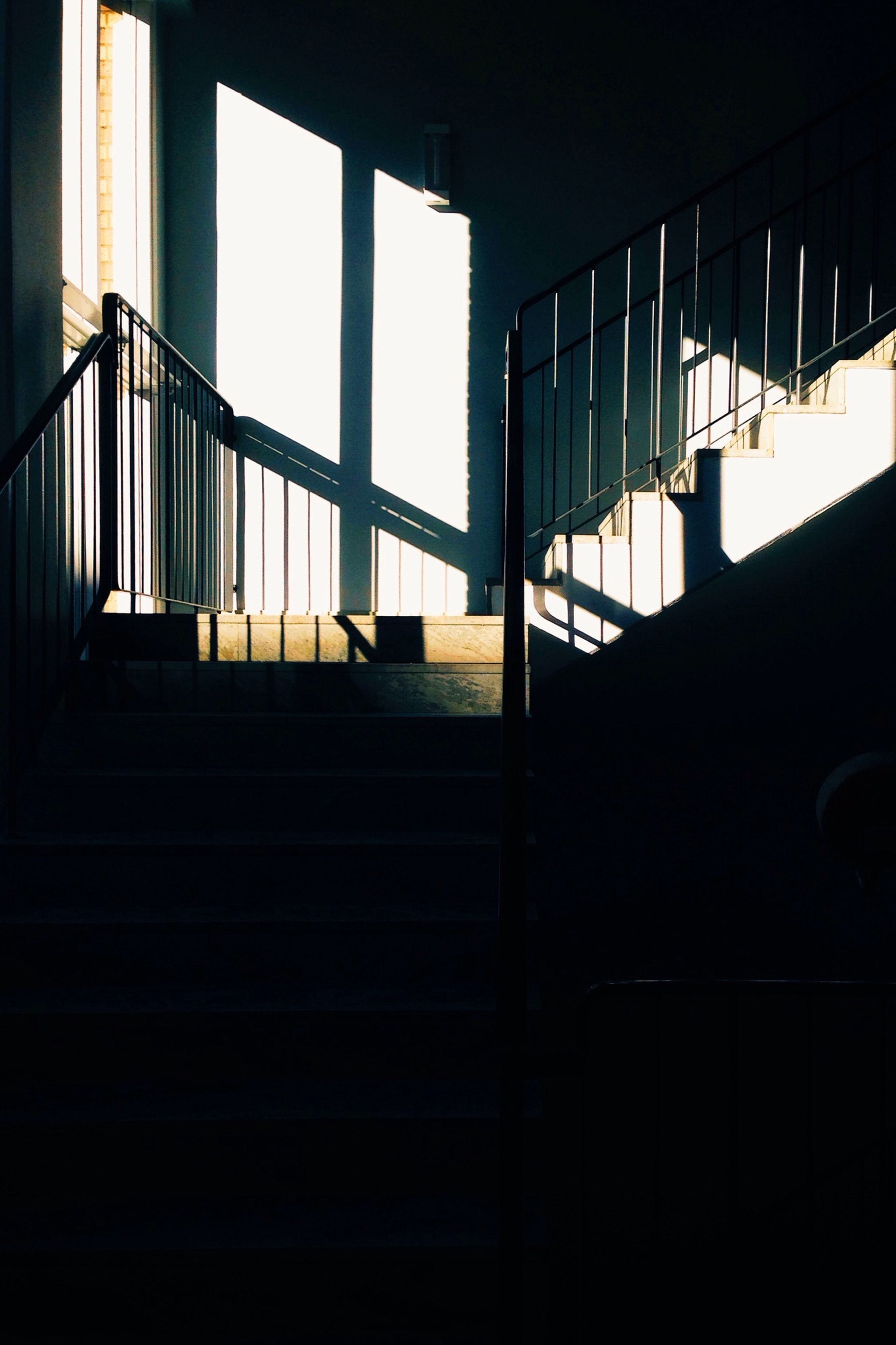 indoors, built structure, architecture, railing, steps, window, staircase, low angle view, steps and staircases, sunlight, building, no people, metal, pattern, silhouette, dark, day, building exterior, glass - material, shadow