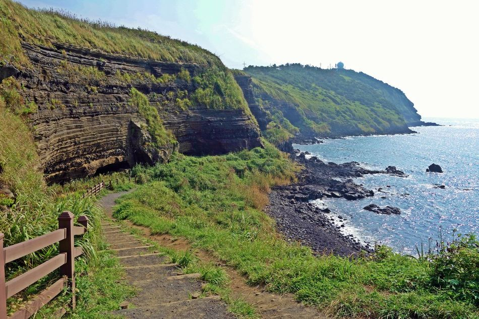 a coast cliff which consists of outcrops of volcanic deposits at a Suwolbong volcanic cone,jeju island,korea,asia Pyroclastic ASIA Basalt Blue Cliff Coast Cone Deposits Grass Island Jeju Korea Nature Outcrop Rock Sea Sky Stiff Suwolbong Travel Trip Tuff Volcanic  Wave White