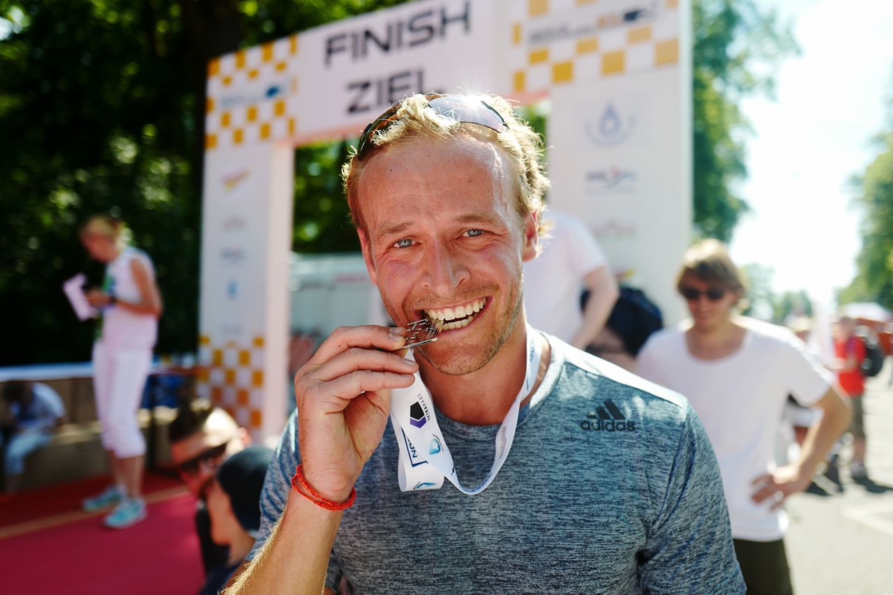 EyeEm Selects Looking At Camera Outdoors Incidental People Smiling Front View Portrait Focus On Foreground Lifestyles Real People Leisure Activity Day One Person Cheerful Men Eating TRIATHLON Winner City Close-up People Adult