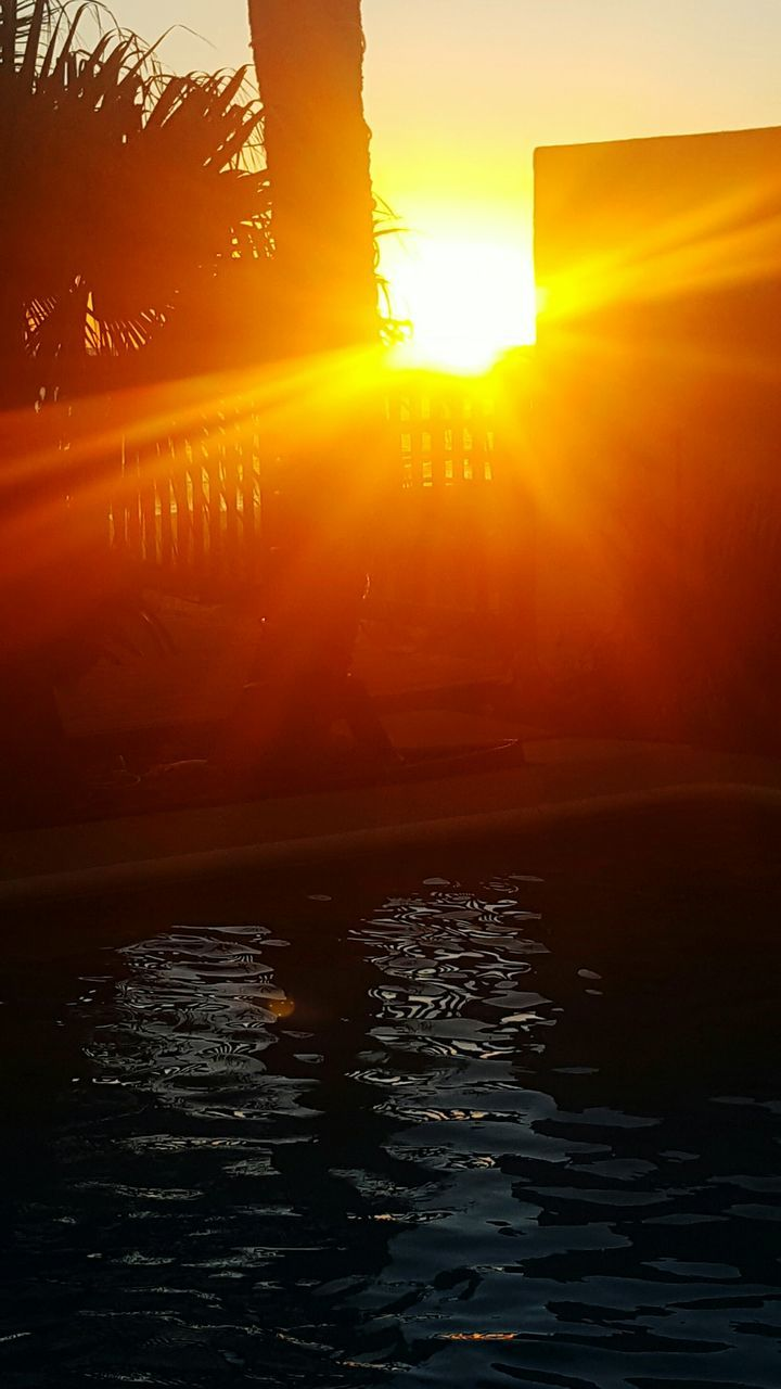 sunset, sunbeam, sun, lens flare, sunlight, orange color, nature, tranquility, silhouette, beauty in nature, water, scenics, outdoors, tranquil scene, reflection, sky, waterfront, no people, lake, day