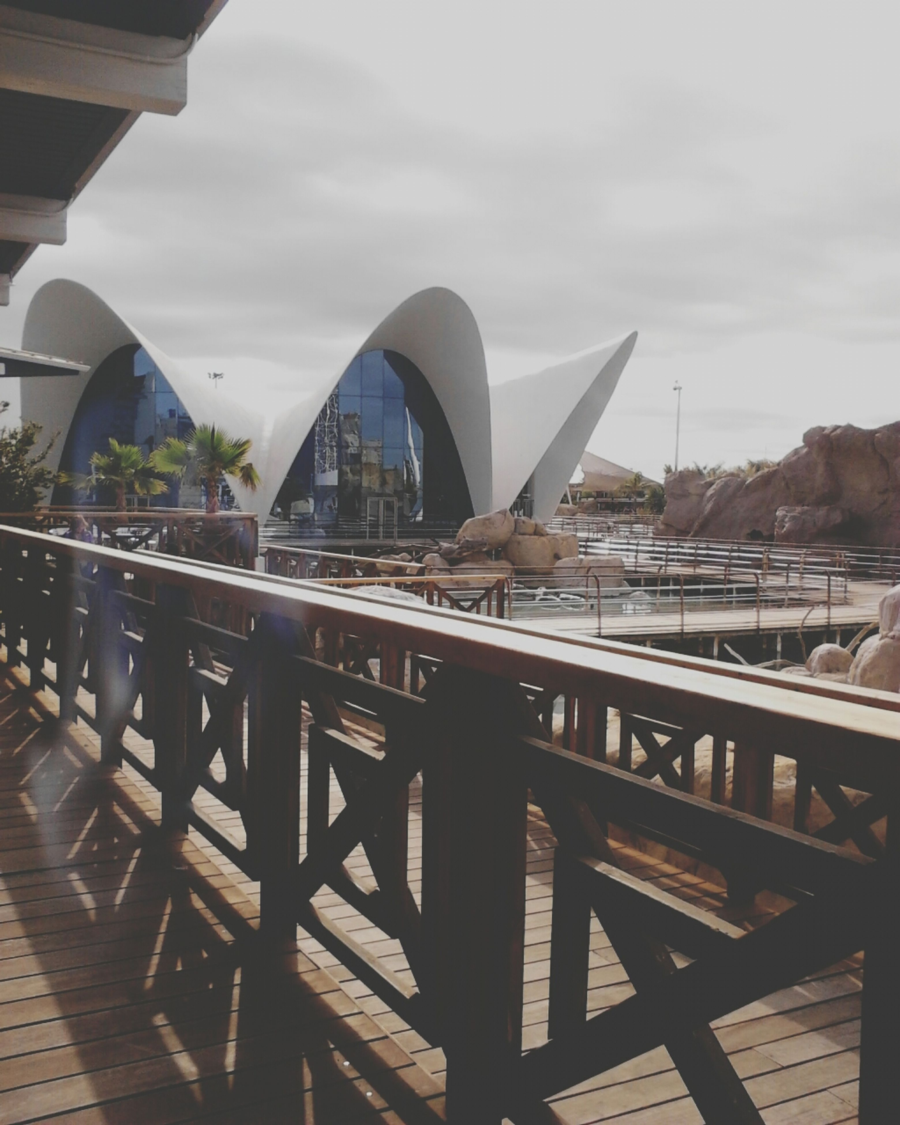 architecture, built structure, sky, building exterior, railing, water, cloud - sky, day, wood - material, river, pier, cloud, outdoors, city, no people, bridge - man made structure, lake, transportation, nature, reflection