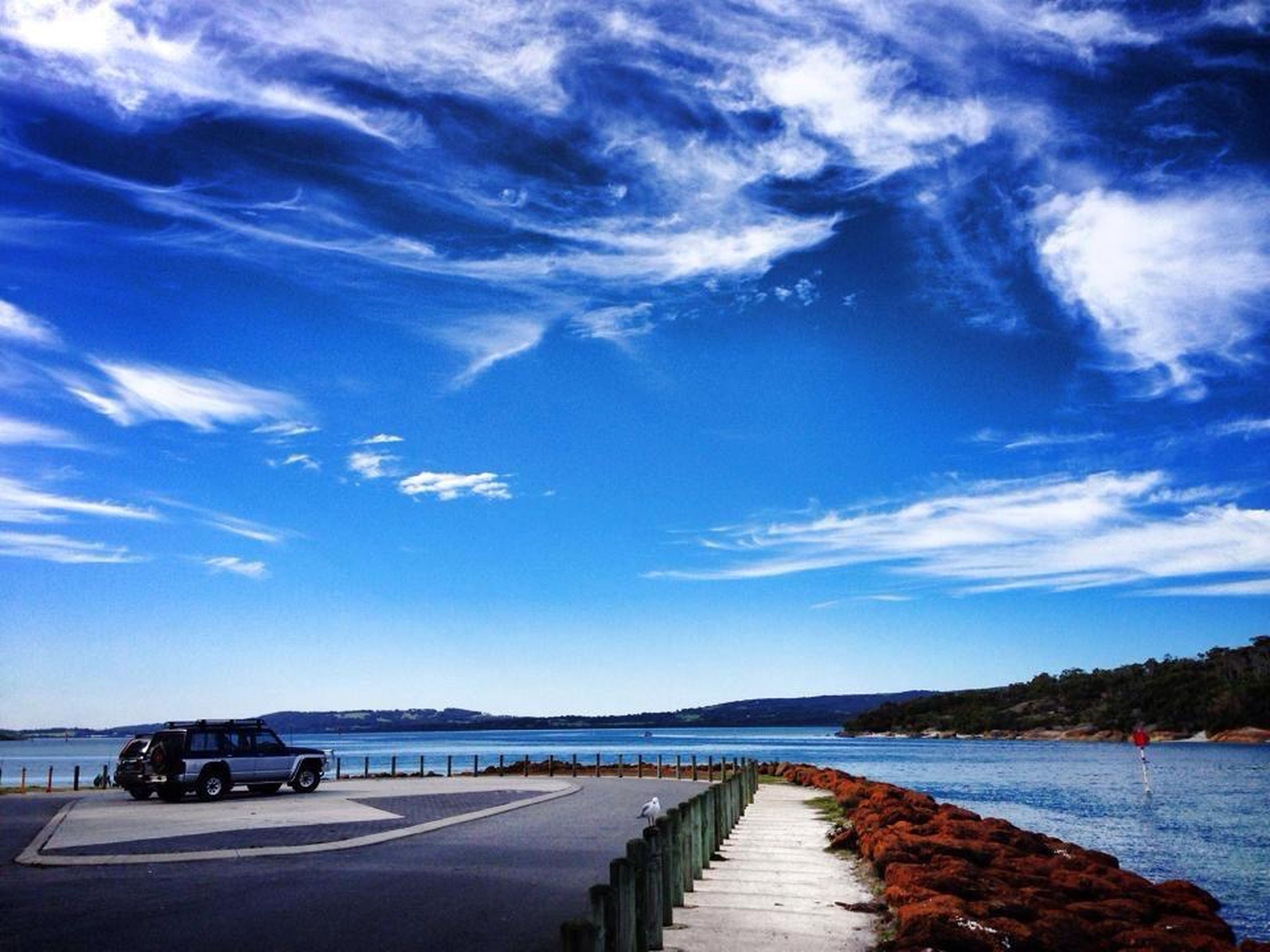 sky, the way forward, water, cloud - sky, sea, transportation, tranquil scene, tranquility, cloud, diminishing perspective, road, nature, scenics, beauty in nature, cloudy, blue, vanishing point, horizon over water, outdoors, beach
