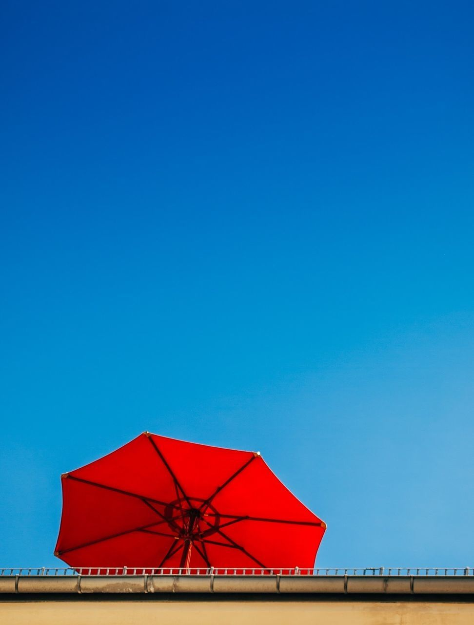 Low Angle View Of Red Umbrella By Wall Against Clear Blue Sky
