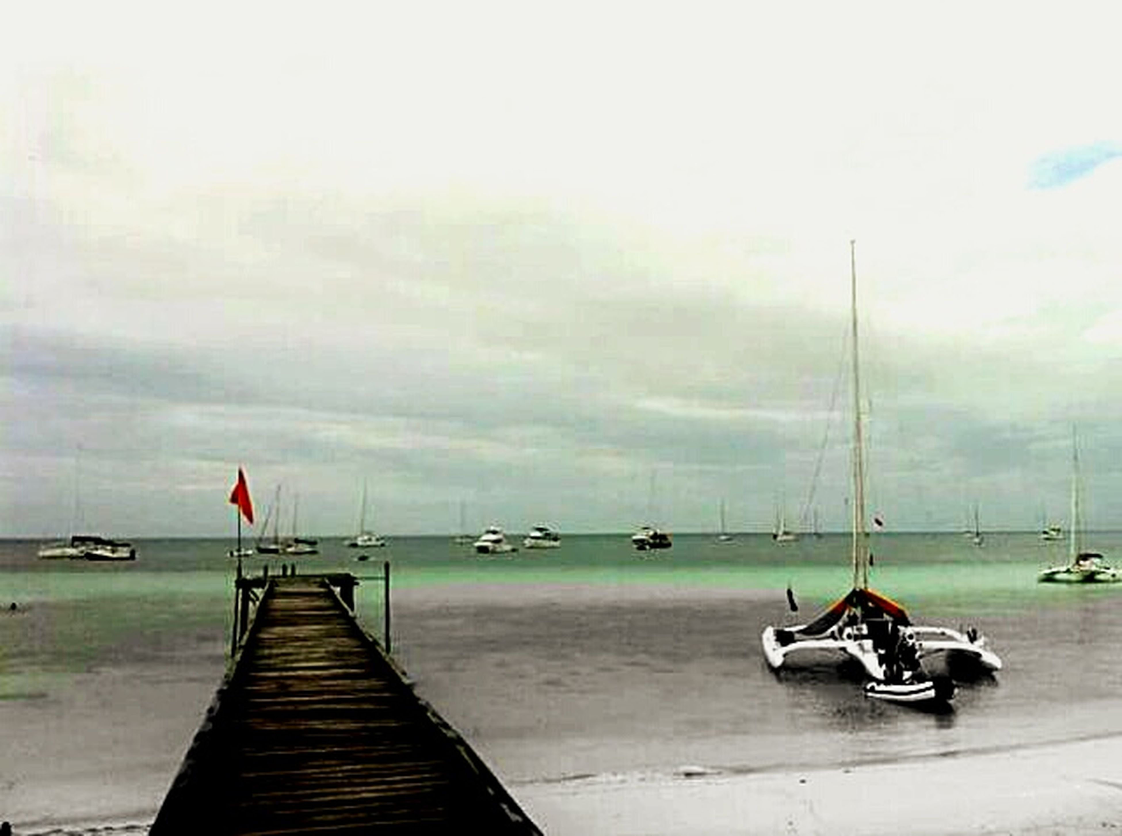 transportation, sky, sea, nautical vessel, mode of transport, water, the way forward, pier, cloud - sky, boat, moored, overcast, cloudy, horizon over water, weather, diminishing perspective, outdoors, empty, built structure, nature