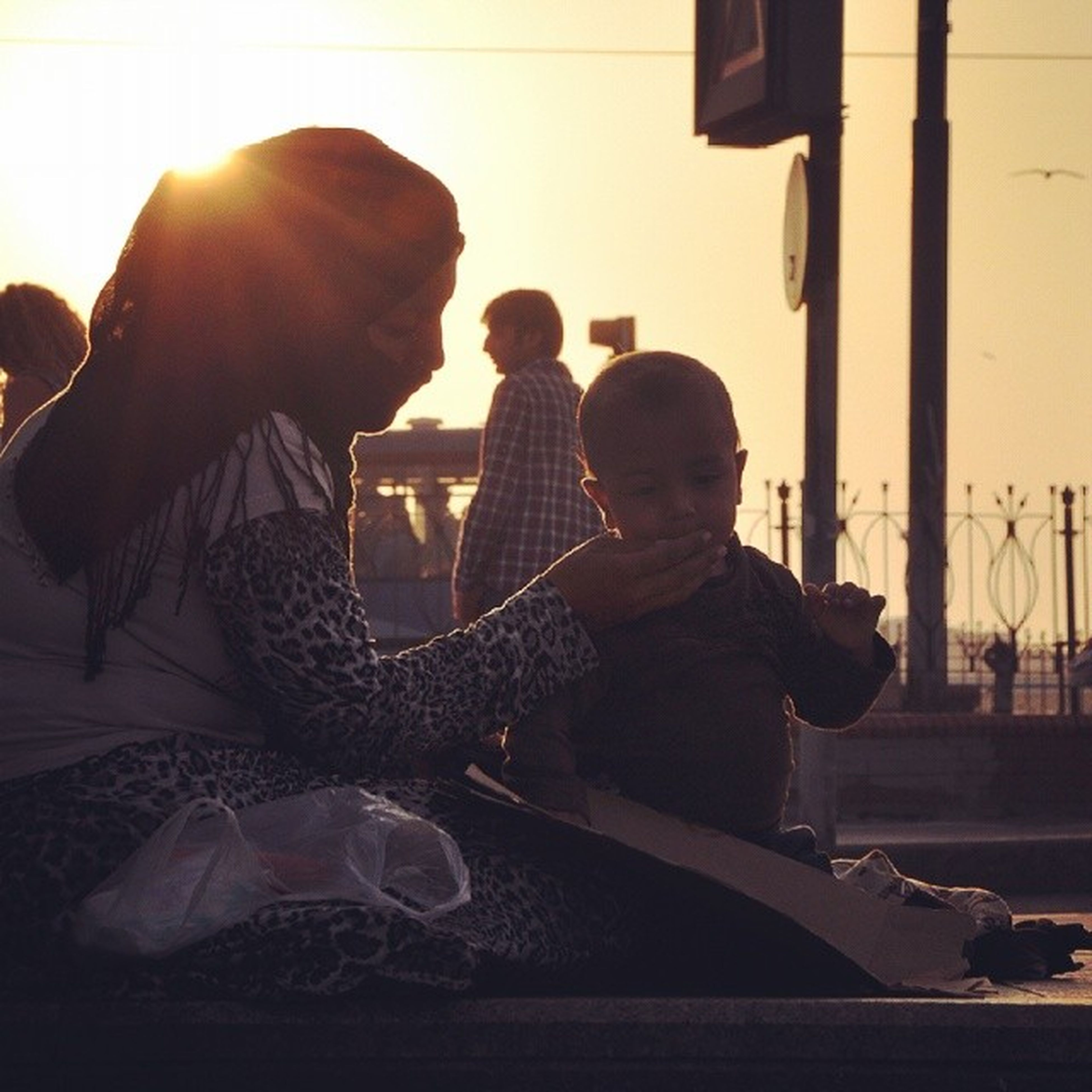 lifestyles, leisure activity, sitting, sunlight, men, sun, sunbeam, rear view, casual clothing, togetherness, silhouette, person, full length, relaxation, sunset, lens flare, side view