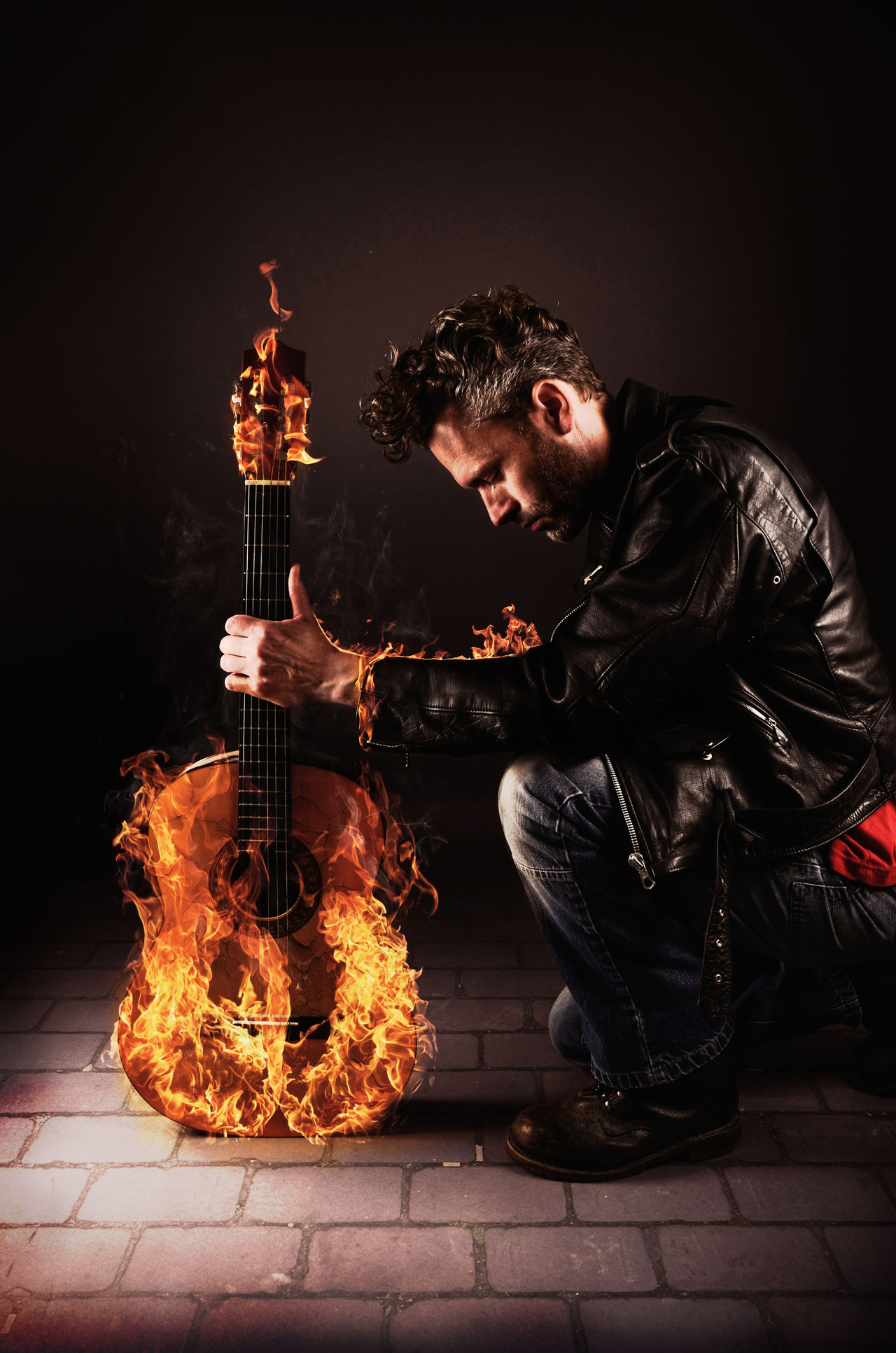 Burning guitar Burn Burning Burning Casual Clothing Crouching Fire Full Length Guitar Holding Hot Indoors  Leather Jacket Leisure Activity Mid Adult Music Musician Night One Man Only One Person People Real People Sitting Standing Young Adult