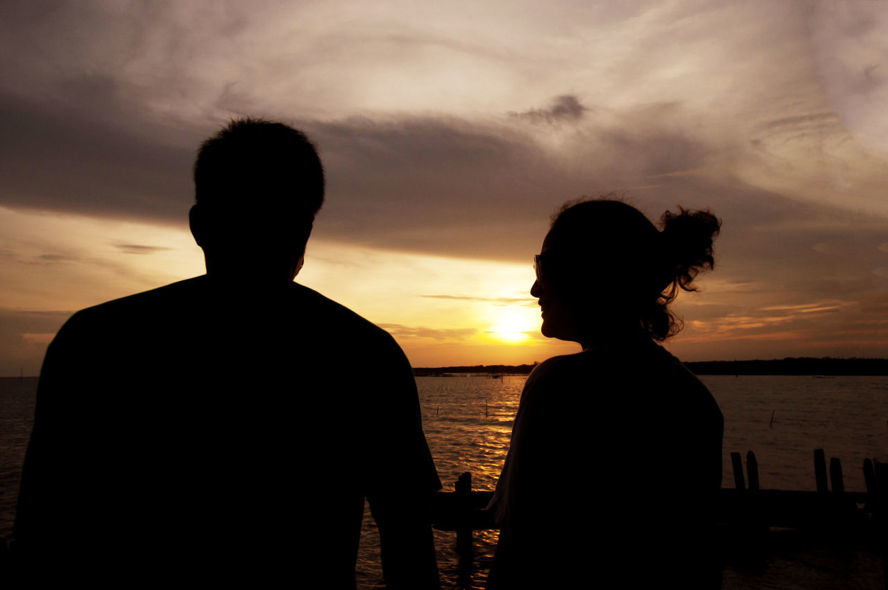 Silhouette Man And Woman Standing Against Sea During Sunset