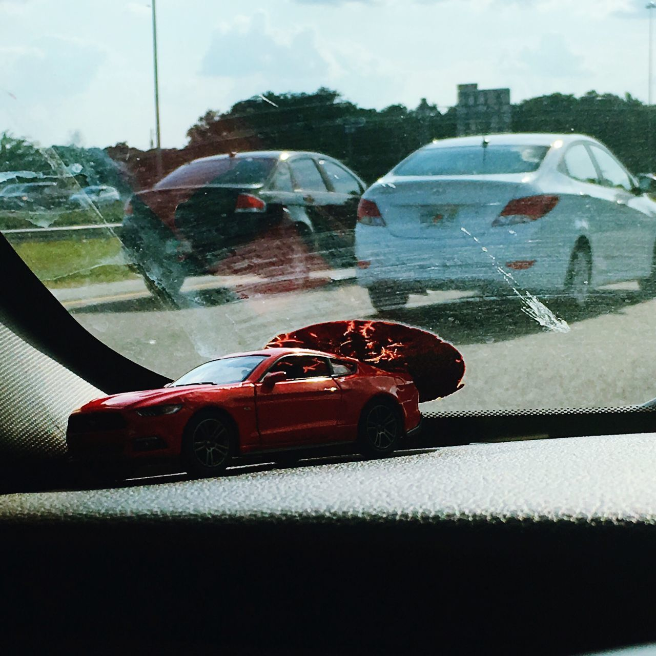 Red Toy Car on my Dashboard , Slid to the side almost out onto the Traffic !