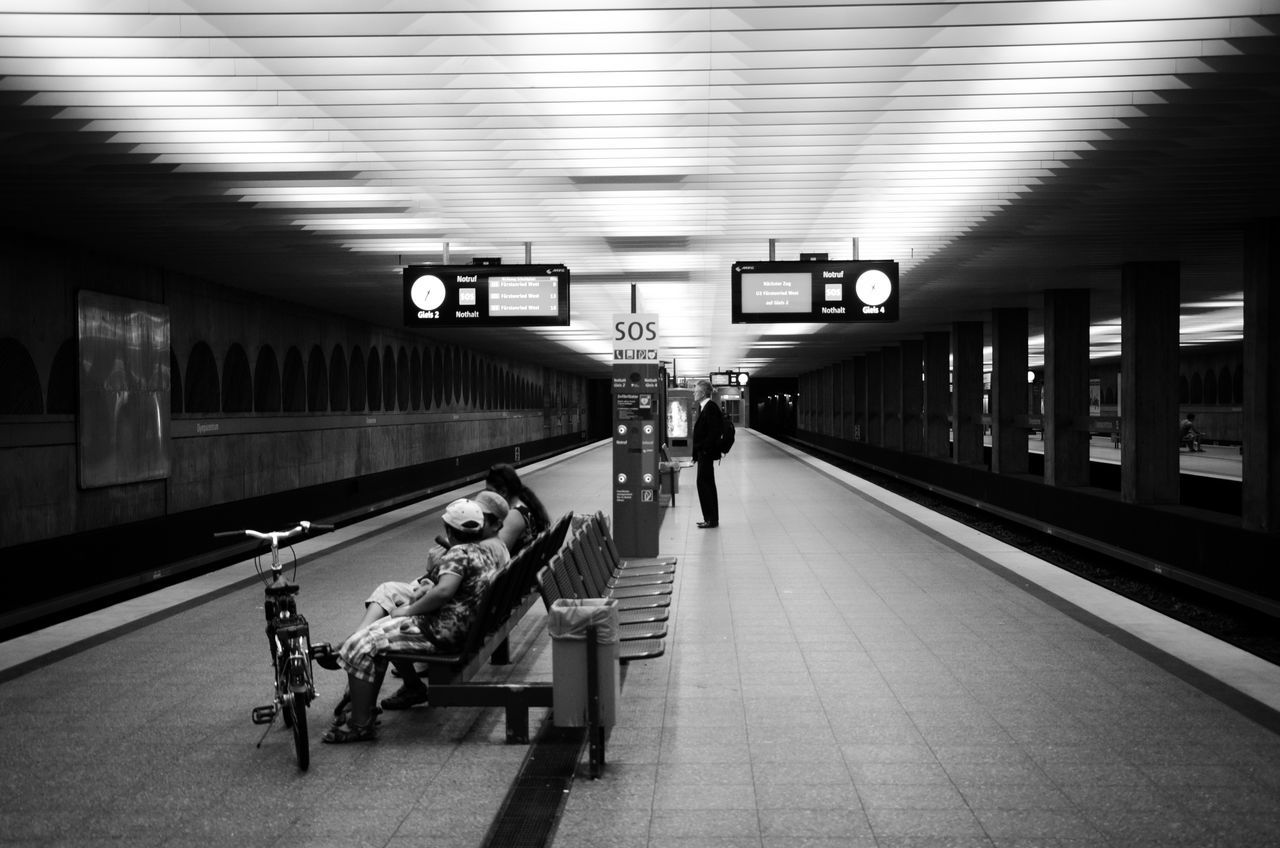transportation, real people, public transportation, rail transportation, railroad station platform, travel, full length, illuminated, railroad station, train - vehicle, indoors, mode of transport, journey, men, sitting, two people, lifestyles, women, subway train, day, people