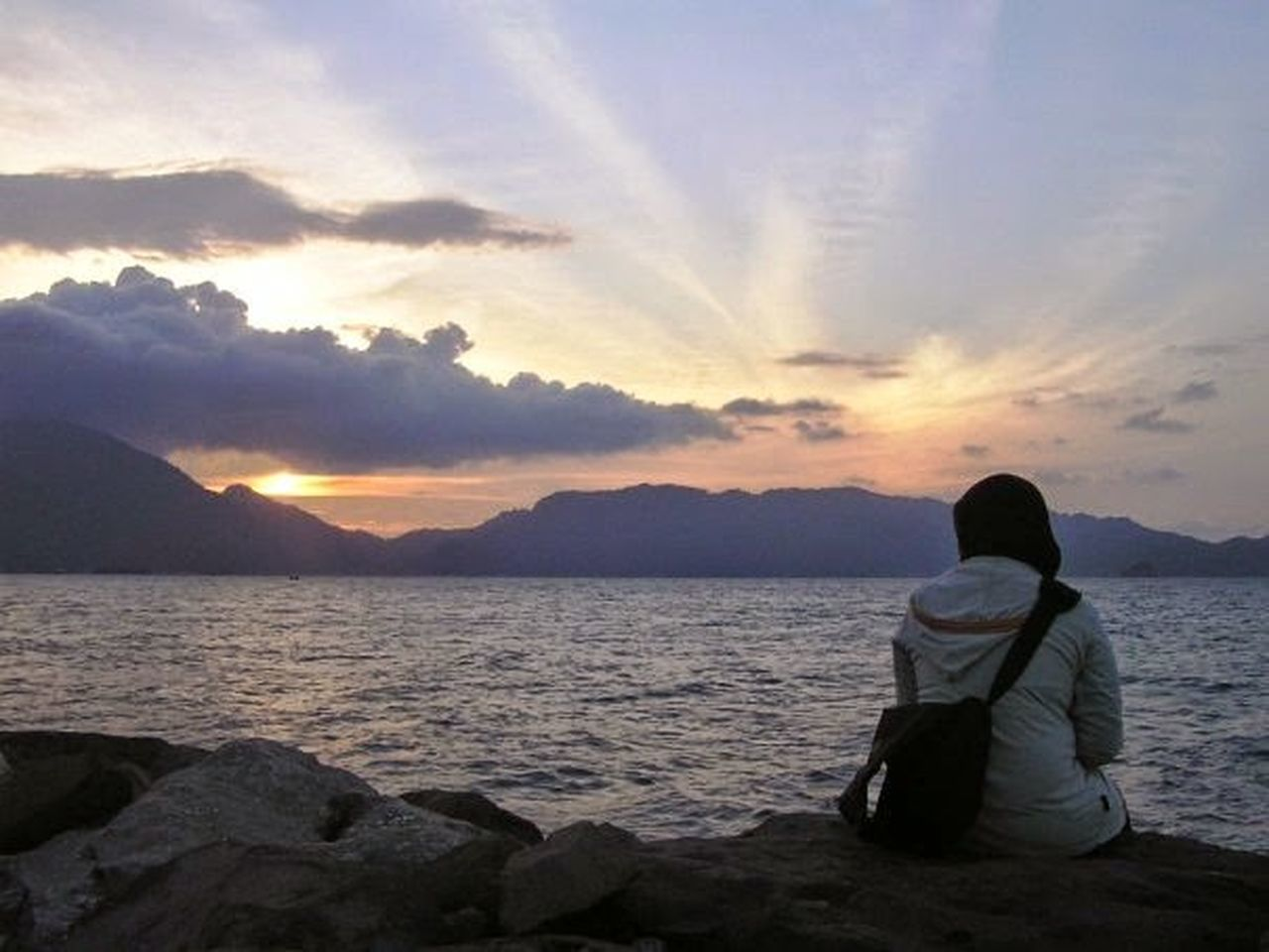 sunset, sitting, rear view, tranquil scene, cloud - sky, sea, relaxation, only women, sky, rock - object, mountain, scenics, zen-like, one woman only, looking at view, adults only, one person, vacations, adult, beauty in nature, people, beach, tranquility, spirituality, water, nature, full length, outdoors, women, horizon over water, night, young adult