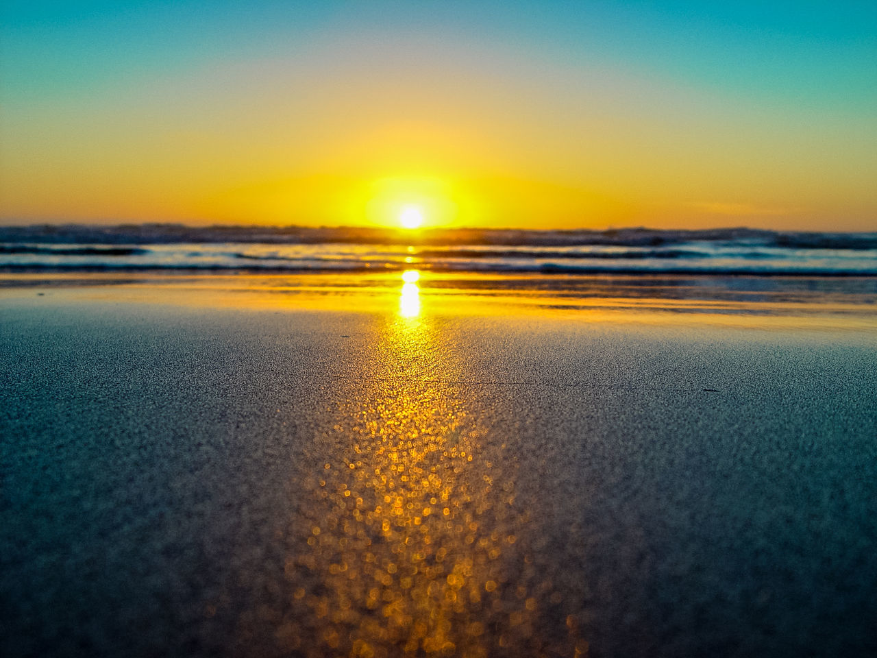sunset, beach, beauty in nature, sea, scenics, nature, sun, tranquil scene, sunlight, tranquility, sky, outdoors, no people, water, sand, horizon over water, day, pebble beach