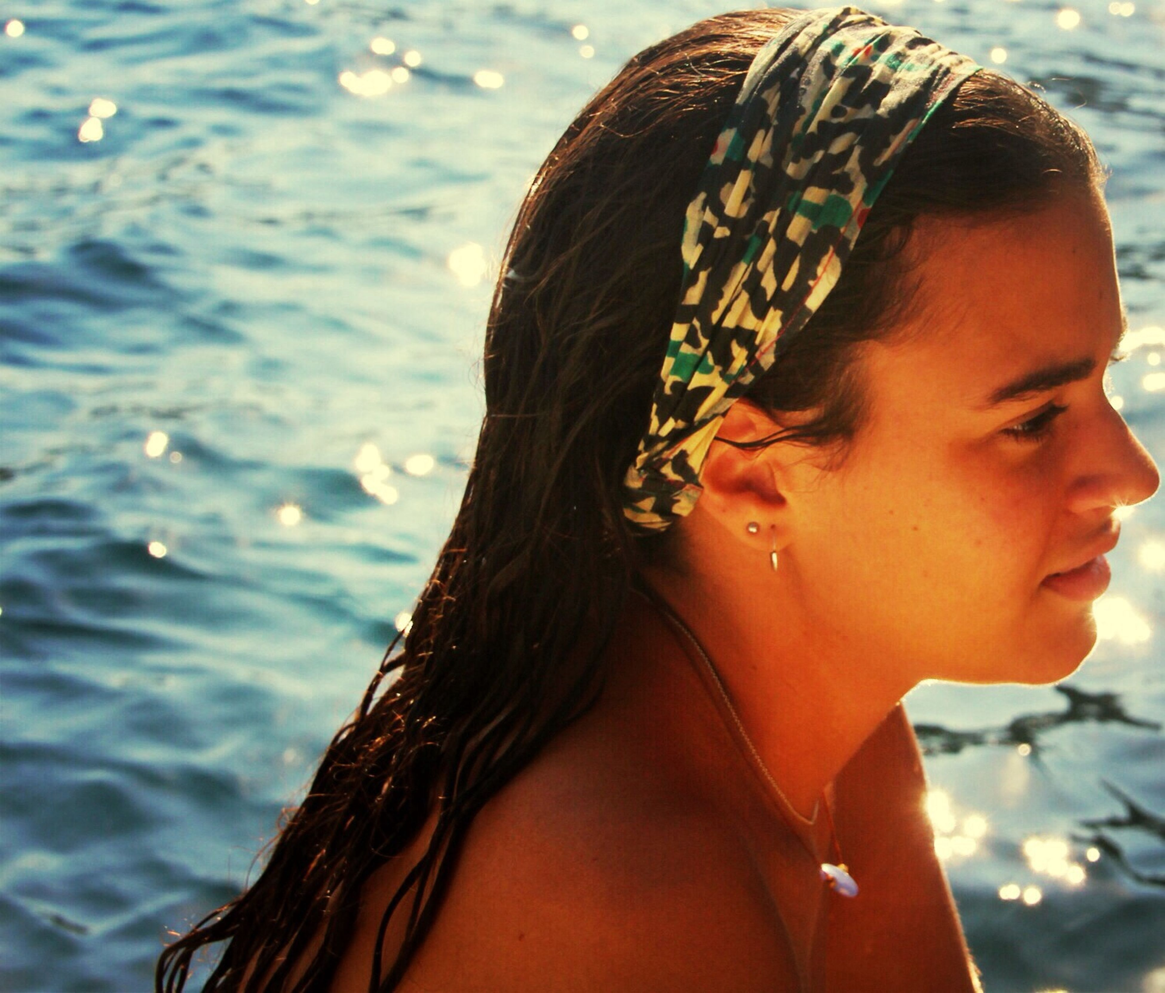 headshot, focus on foreground, young adult, close-up, water, person, lifestyles, leisure activity, young women, portrait, sea, human face, head and shoulders, looking at camera, outdoors, day, front view, side view