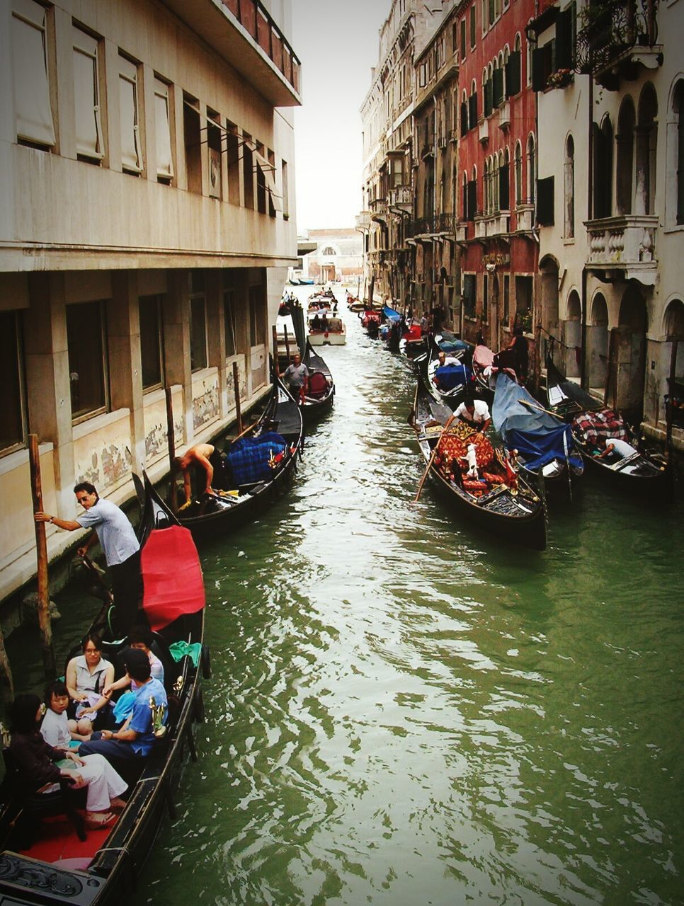 nautical vessel, canal, transportation, architecture, mode of transport, building exterior, gondola - traditional boat, gondola, real people, built structure, boat, gondolier, men, water, travel destinations, large group of people, day, tourism, travel, outdoors, waterfront, moored, women, vacations, oar, rowing, city, people