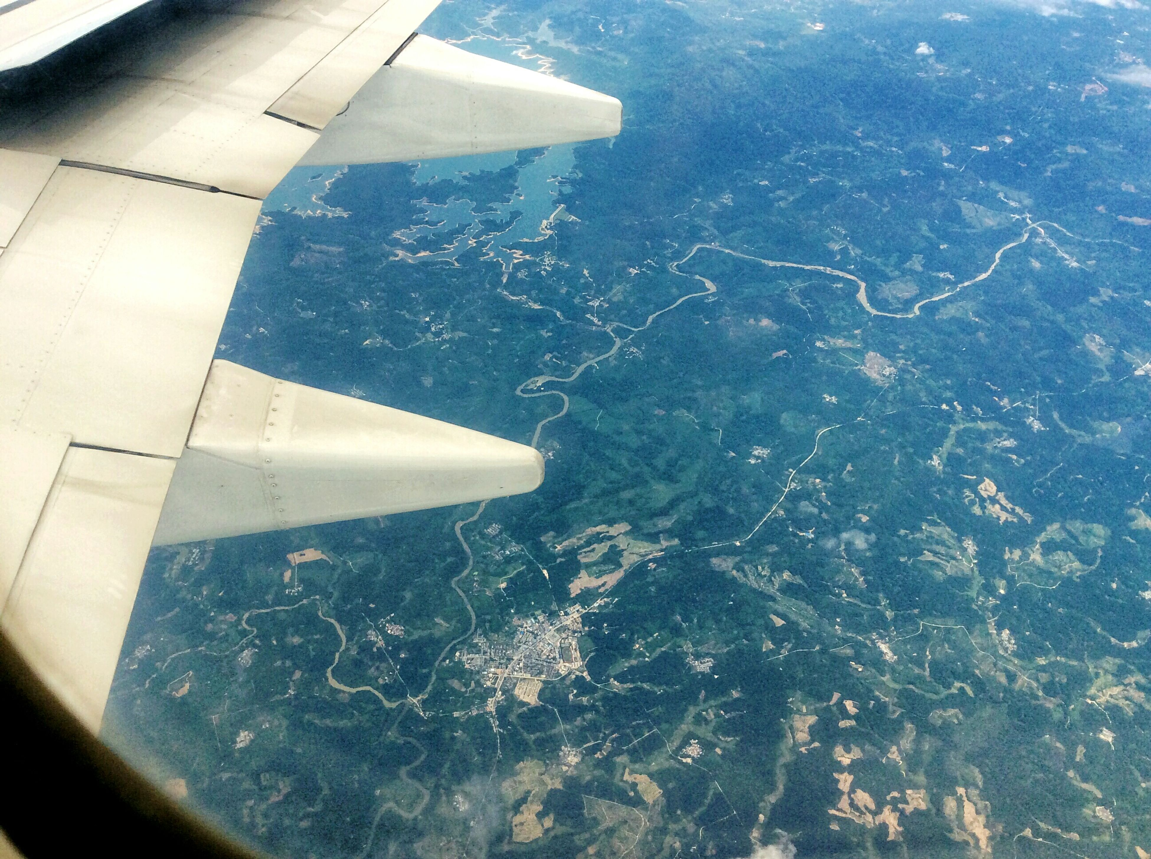 airplane, transportation, air vehicle, aerial view, flying, aircraft wing, mode of transport, part of, mid-air, cropped, travel, on the move, landscape, scenics, journey, nature, beauty in nature, water, sea, mountain