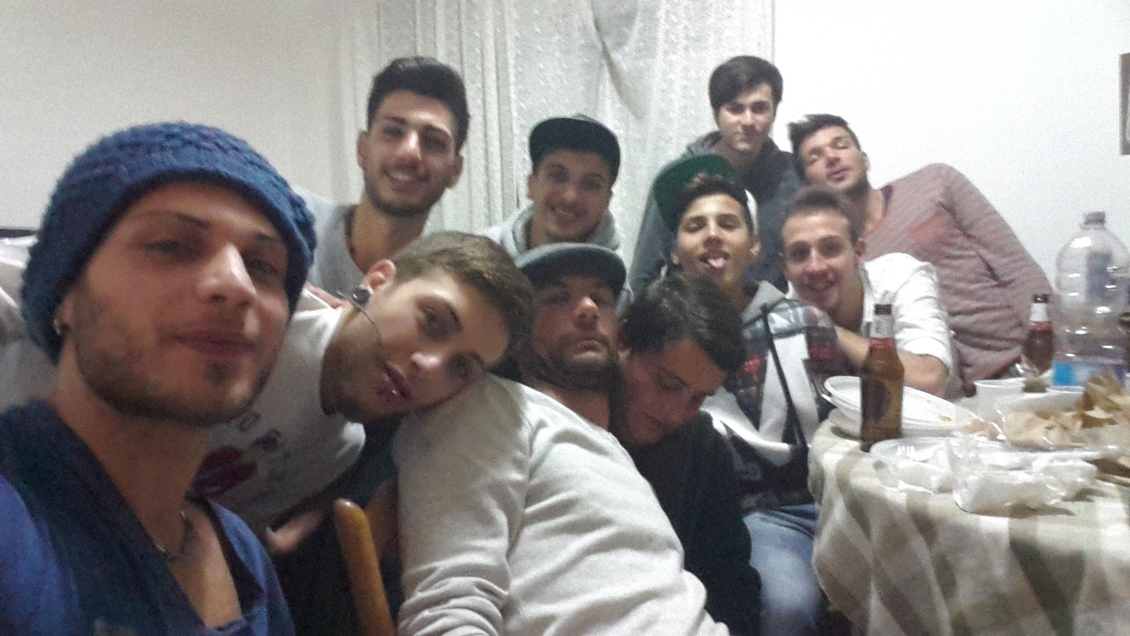 indoors, togetherness, lifestyles, young men, leisure activity, men, bonding, casual clothing, love, friendship, sitting, person, mid adult men, front view, young adult, smiling, side by side
