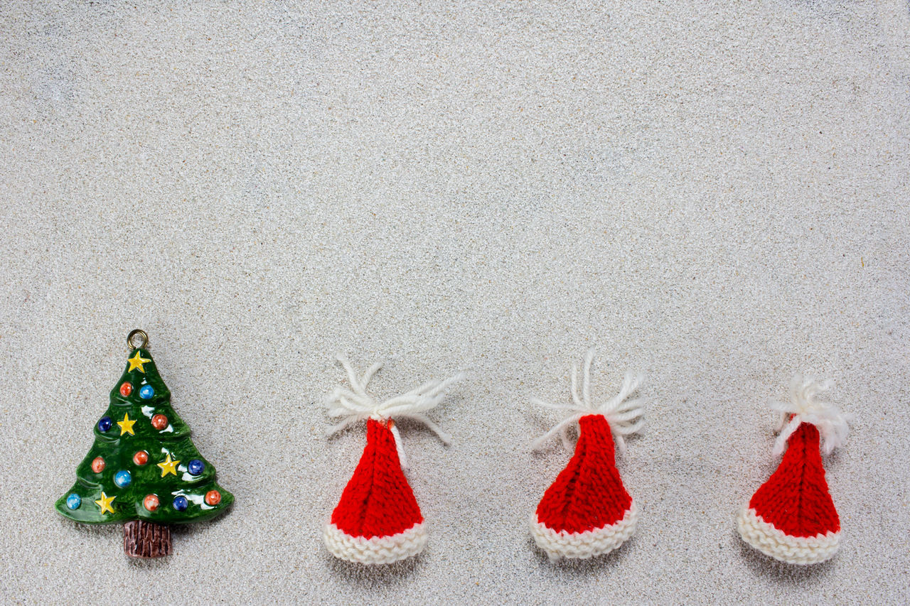 A colorful christmas tree and red christmas hats on white snow Background Cap Celebration Christmas Claus December Decoration Festive Holiday Merry Santa Sky Snow Tree White Winter Xmas
