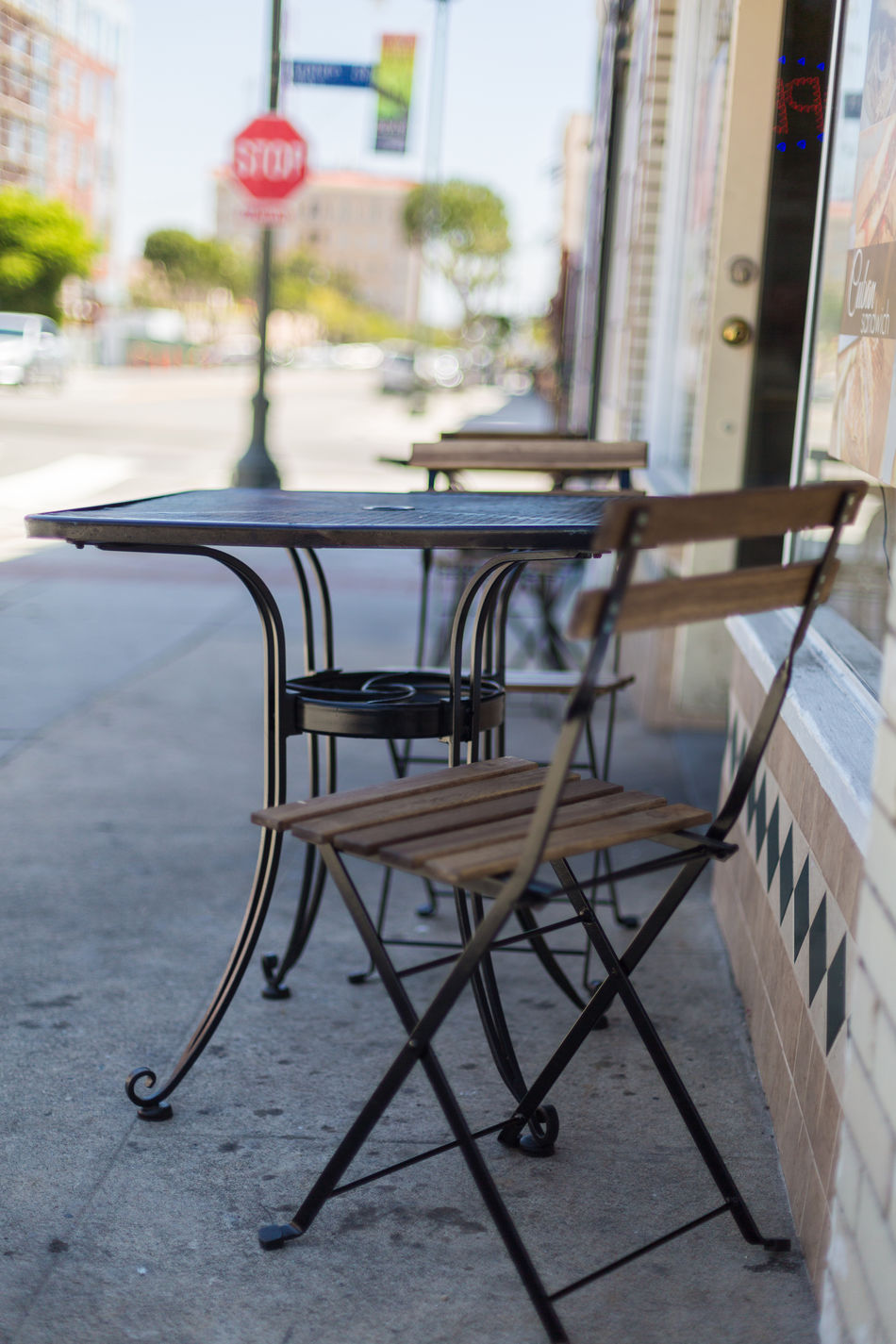 cafe tables and chairs Architecture Building Building Exterior Cafe Cafe Entrance Chairs City Close-up Day Focus On Foreground Metal Tables Morning No People Outdoors Patio Roads Shade Shaded Shallow Depth Of Field Stop Sign Street Tables Town Urban Windows
