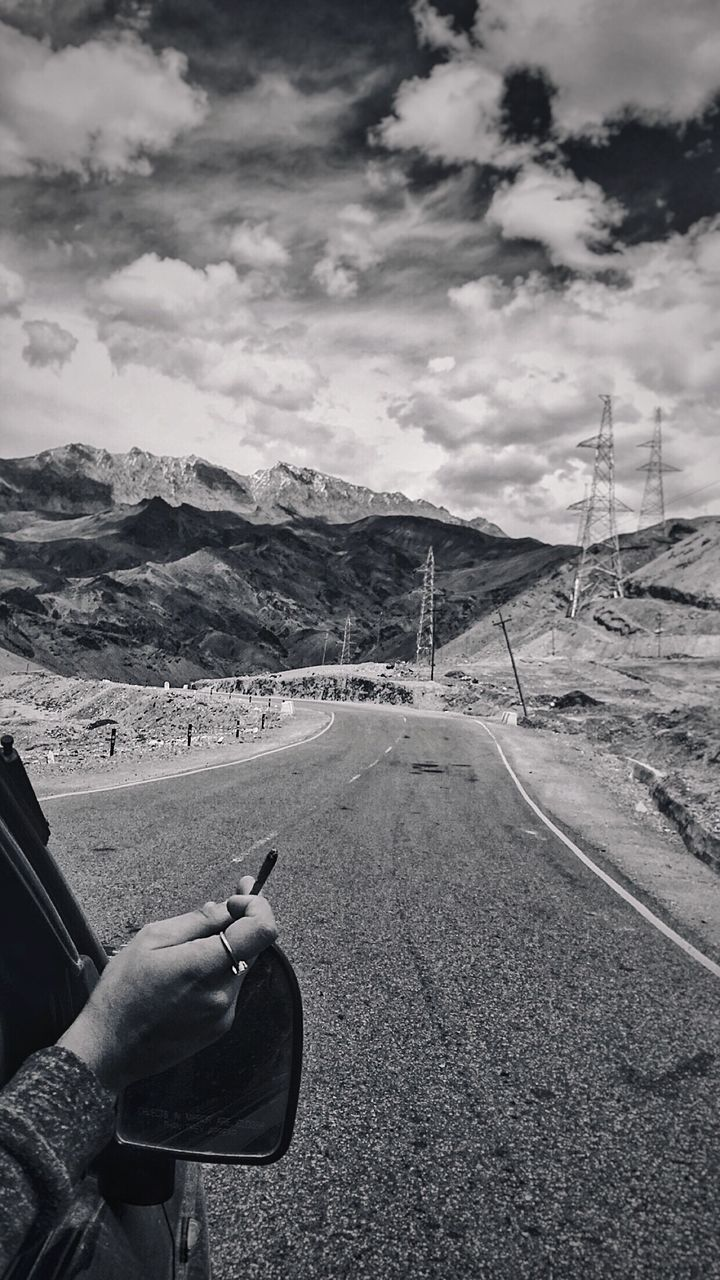 real people, one person, road, cloud - sky, sky, mountain, transportation, day, human body part, lifestyles, outdoors, men, landscape, low section, nature, scenics, human hand, adult, people