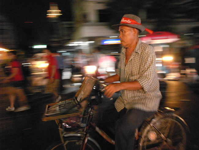 a red shirt lottery seller on his bicycle 2010 Bangkok Bicycle Documentary Photography Ratchaprasong Street Photography Streetphotography Thailand Up Close Street Photography