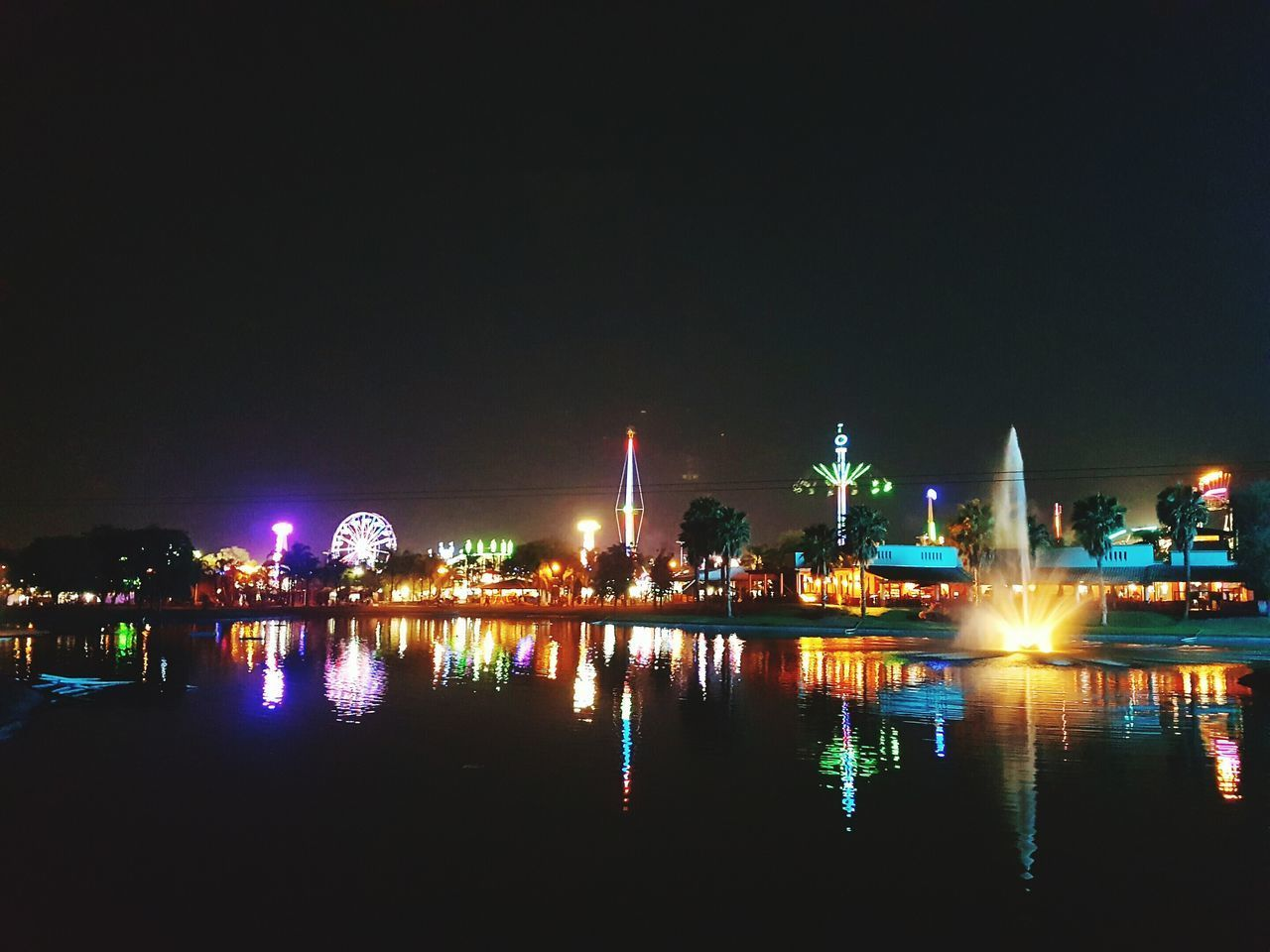 night, illuminated, water, reflection, built structure, waterfront, architecture, building exterior, city, river, outdoors, sky, arts culture and entertainment, multi colored, travel destinations, no people, clear sky, cityscape, urban skyline