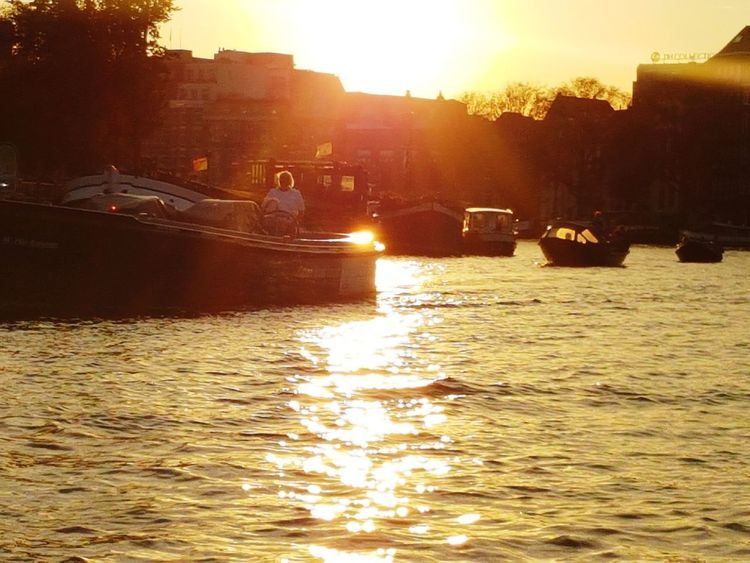 Sunset Sunlight Nautical Vessel River Outdoors Water No People Sun Travel Summer Vacations Nature Sky Day Architecture City Tree Amsterdam Canal Amsterdam Canal Travel Photography Travelling Travel Destinations City Tranquility