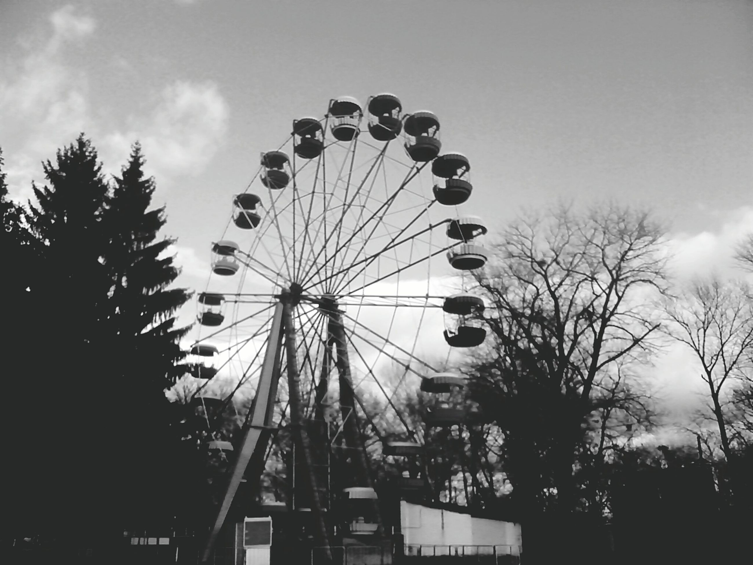 low angle view, ferris wheel, amusement park, amusement park ride, arts culture and entertainment, sky, tree, silhouette, built structure, circle, cloud - sky, outdoors, architecture, day, large, fairground, cloud, fun, no people, fairground ride