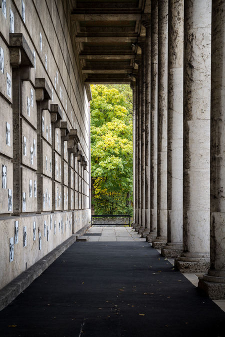 Colonnade perspective at the Haus der Kunst in Munich, leading towards the Englisher Garten, city park. Architecture Austere Colonnade Haus Der Kunst Historic Leading Munich Museum Narrow Natural Vs Artificial Nature Nazi Architecture Neoclassic Perspective Towards Nature,