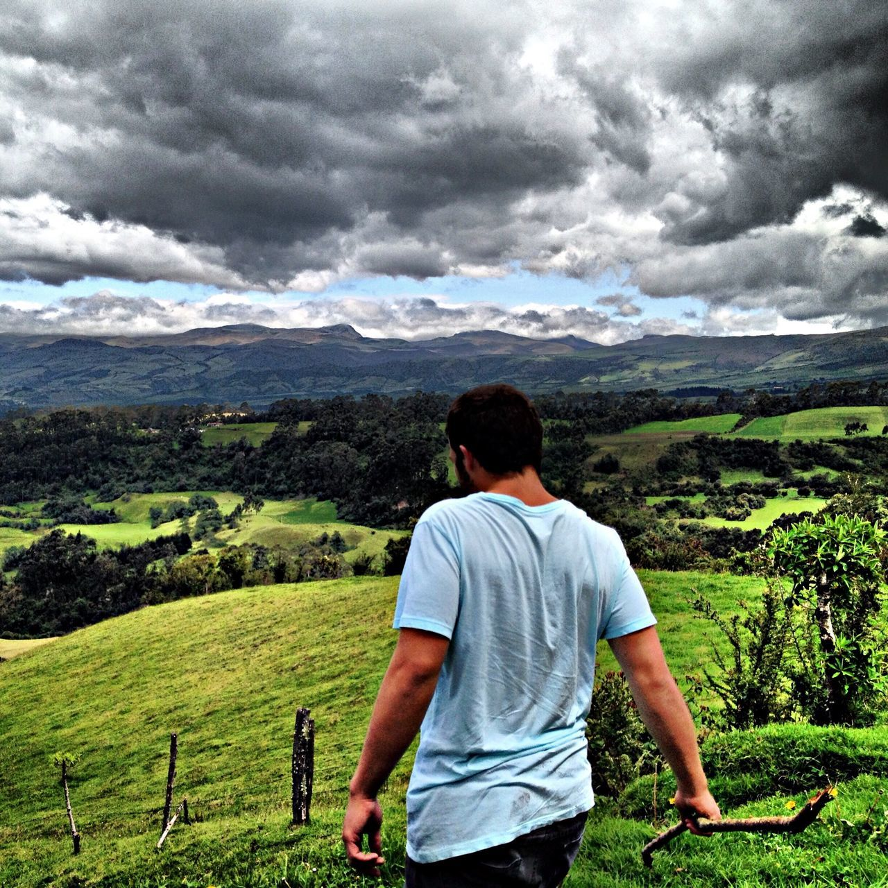 Rear view of a man overlooking landscape below clouds