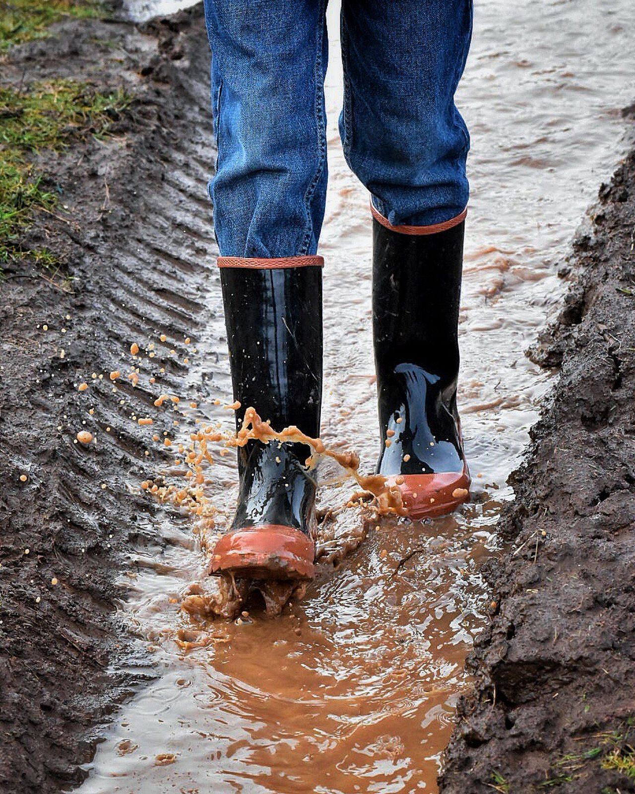 Low Section Human Foot Outdoors Water Human Body Part Human Leg Jeans Casual Clothing Standing Day Shoe Close-up One Person Leisure Activity People Having Fun Puddle Outdoor Photography Adventure Rubber Boots Childhood Puddles Jeans Walking In A Puddle Nature